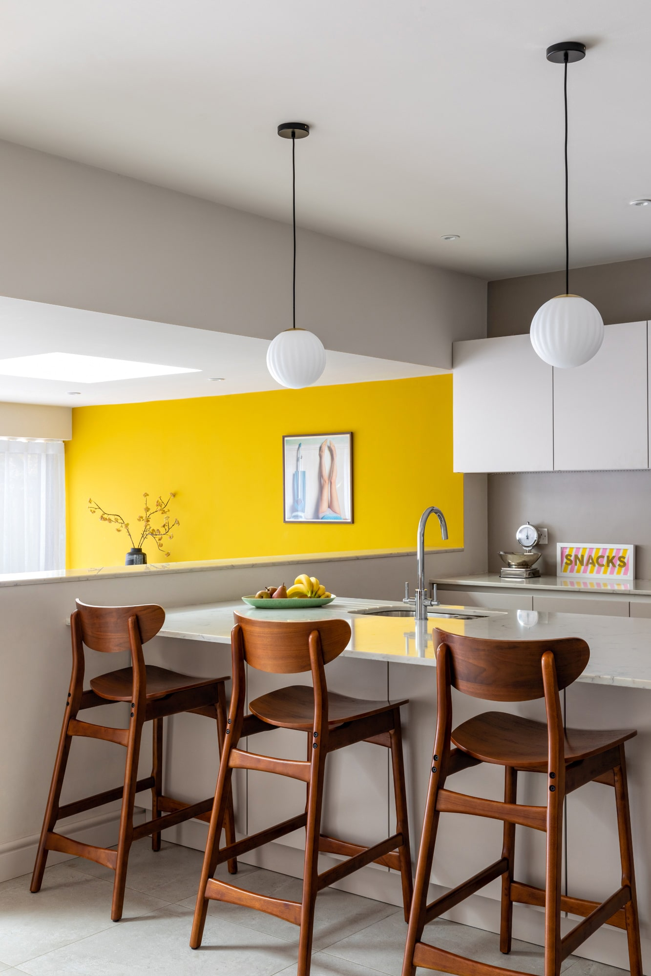 Interior design photo: a view on a white kitchen with white stone worktop, three wooden chairs and a yellow wall on the left side of the kitchen