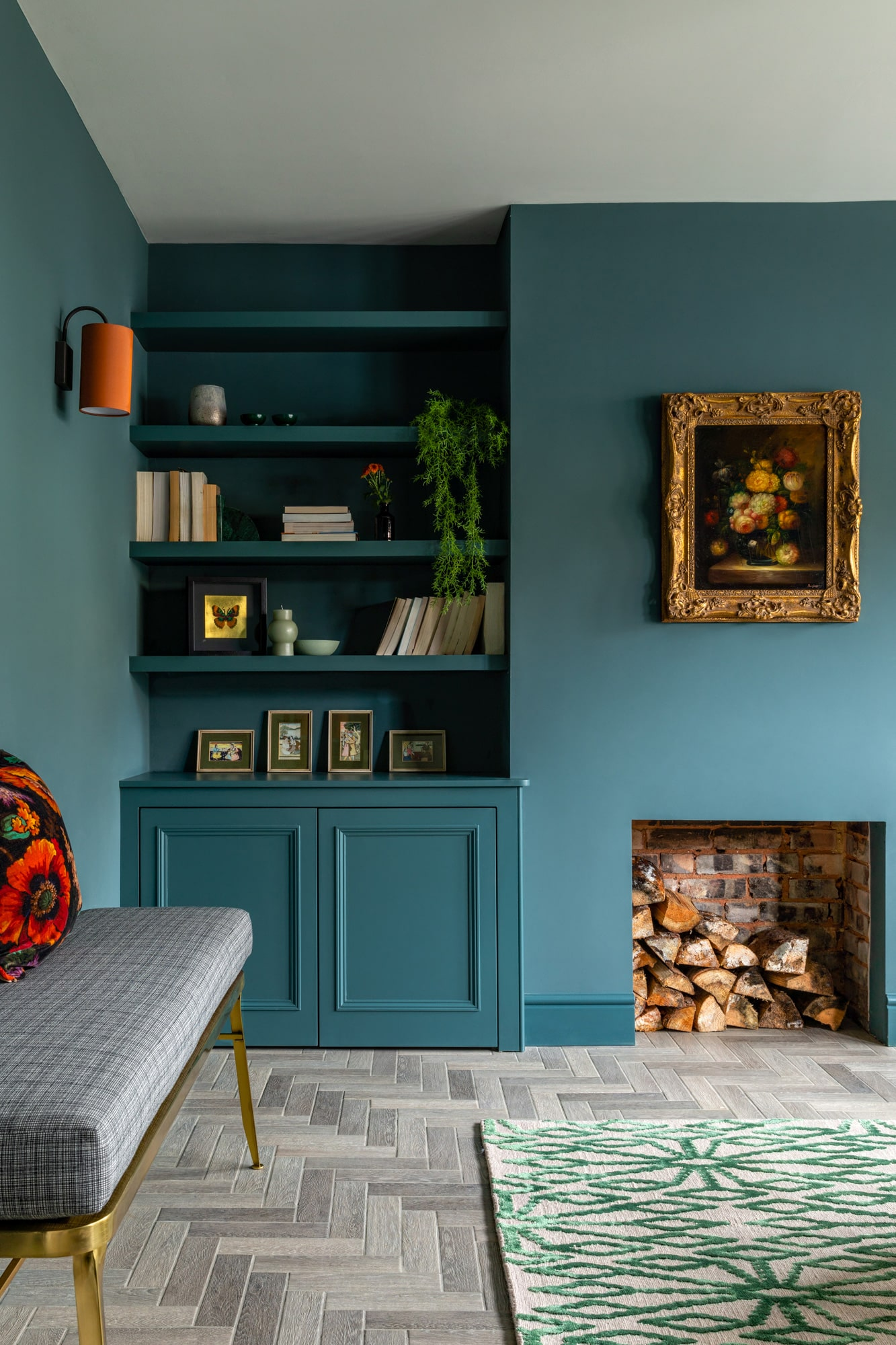 interior design photography: a sitting room with dark blue walls, a fireplace with wood logs, built in shelves and cardboard with plant pots and books