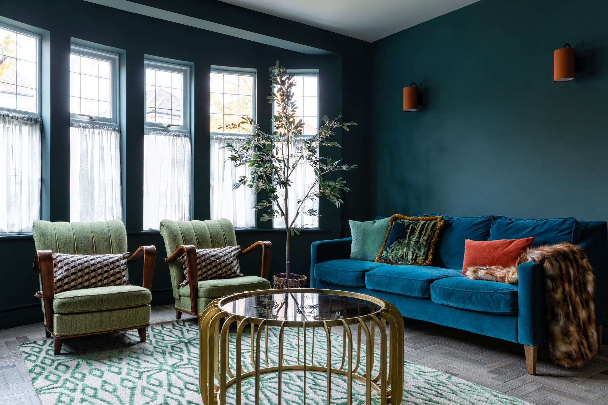 An overview interior design shot: a living room with dark blue walls, teal sofa, two green armchairs and a gold metal coffee table with a glass top