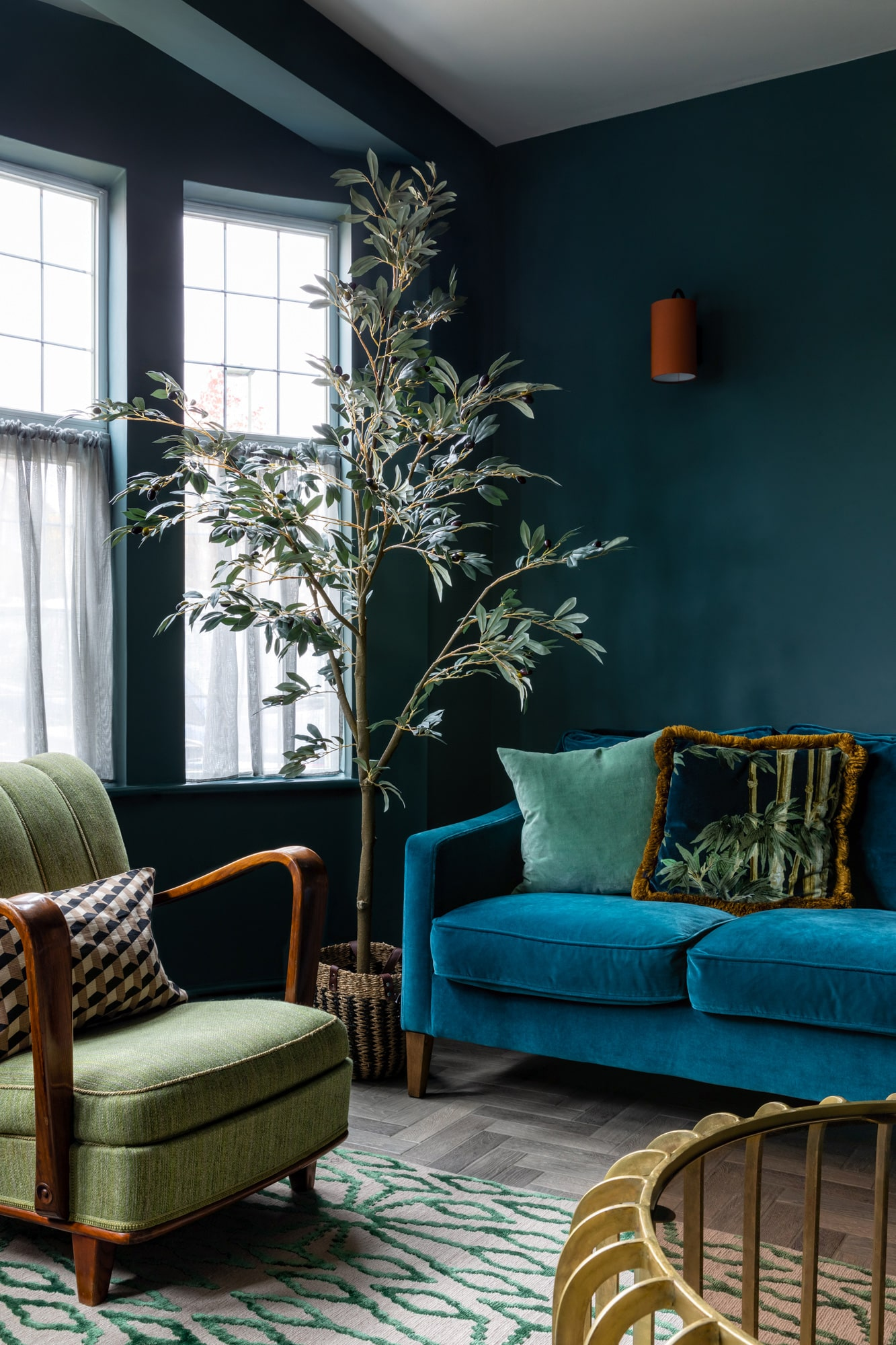 An overview interior design detail image: a living room with dark blue walls, teal sofa, two green armchairs and a gold metal coffee table with a glass top