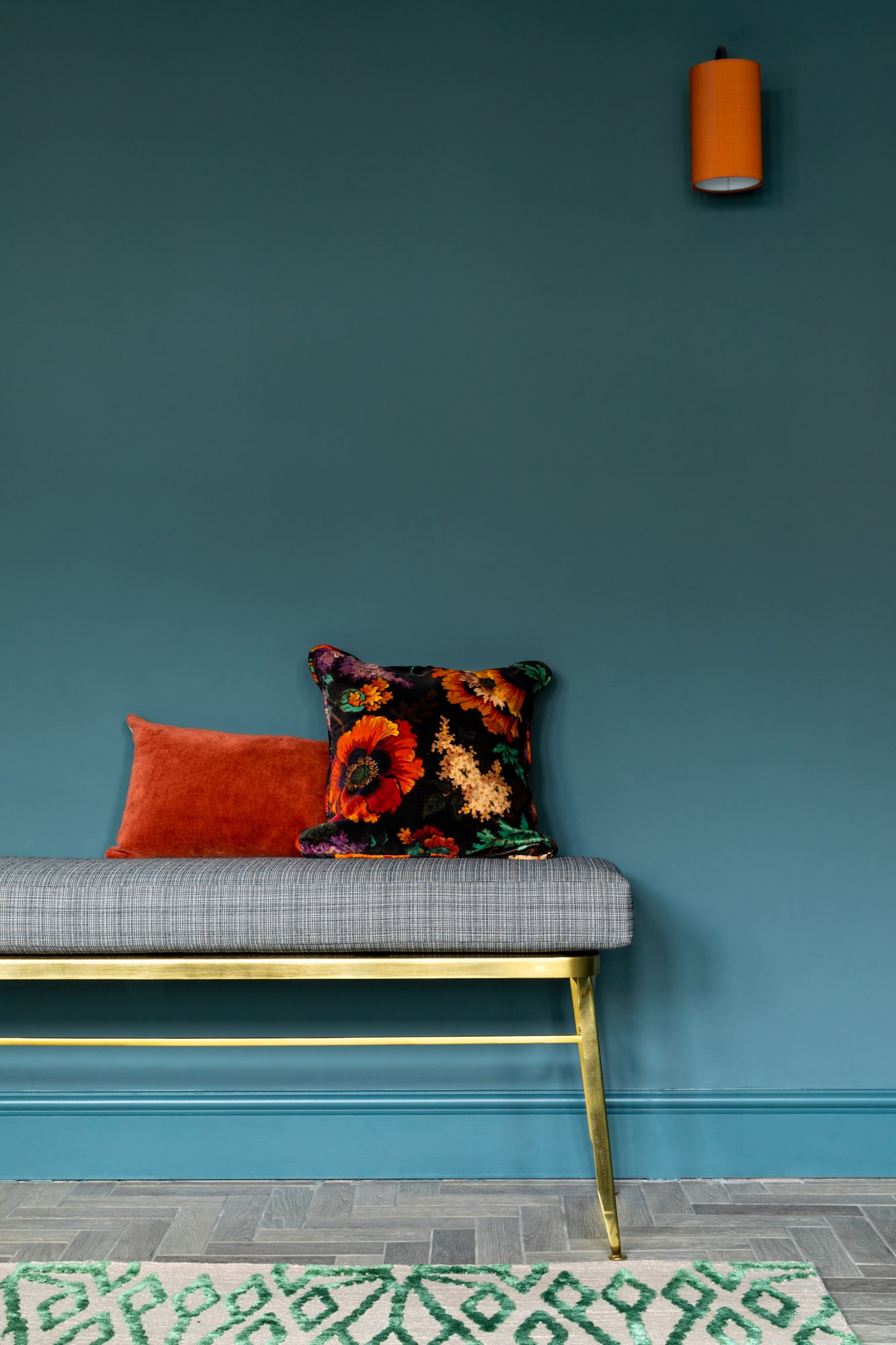 interior design detail photo: dark blue walls with a grey gold bench, and two pillow on top.