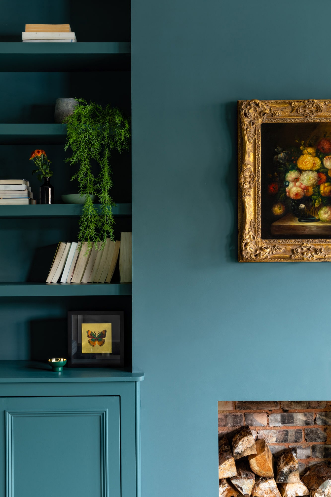 interior design image: a sitting room with dark blue walls, a fireplace with wood logs and a painting above it;  built in shelves and cardboard with plant pot, vase and books