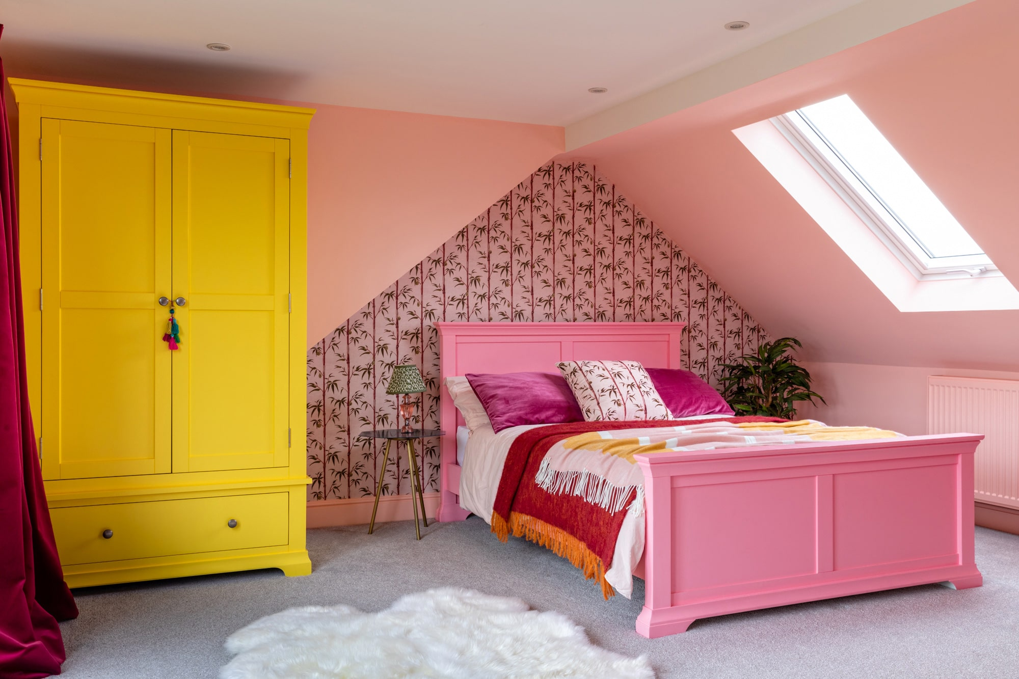 pink girl's bedroom: pink bed, floral wallpapers feature walls, glass bedside table; yellow wardrobe