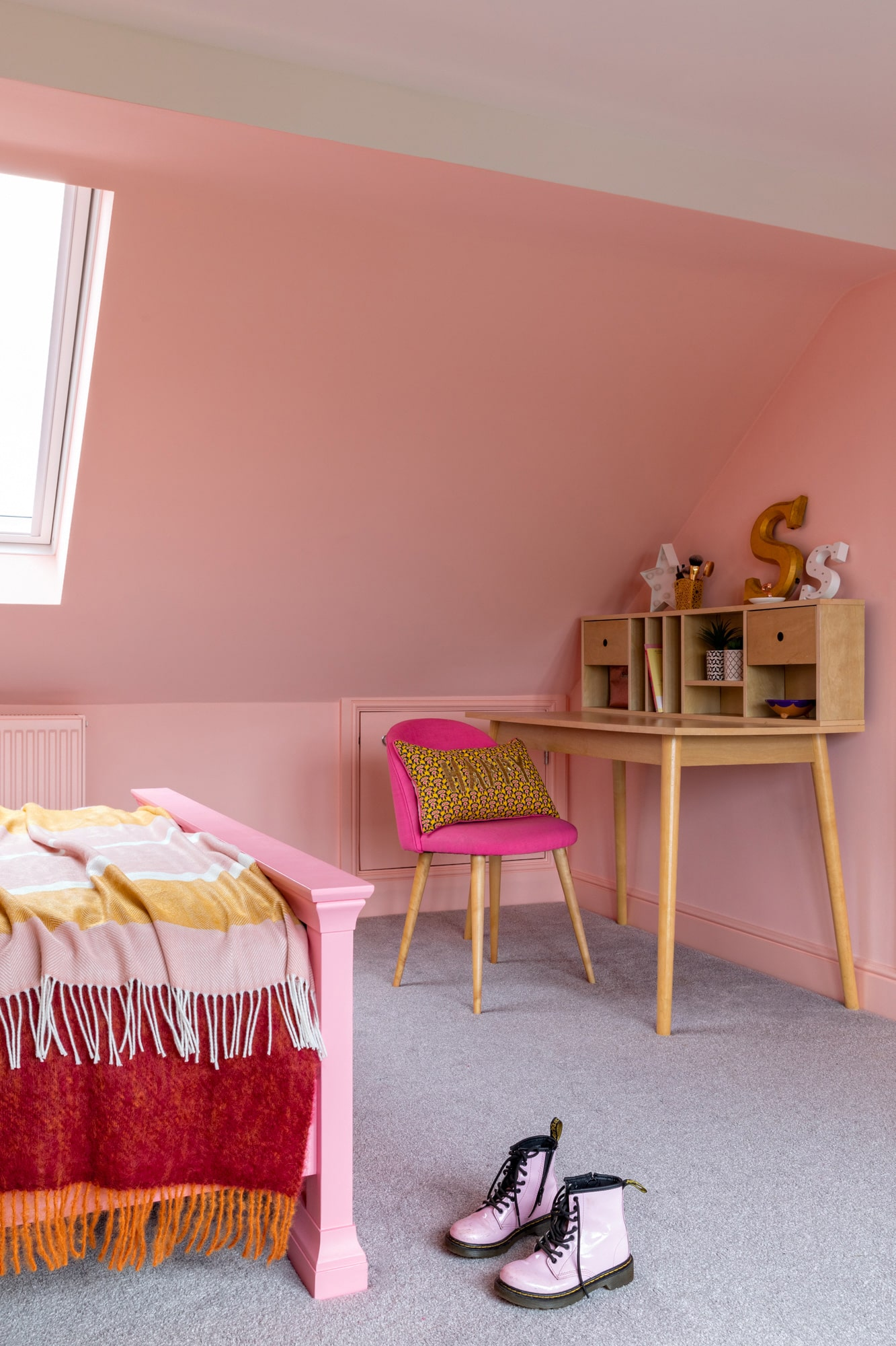 pink girl's bedroom: pink bed, wooden desk with pink chair, ceiling windows