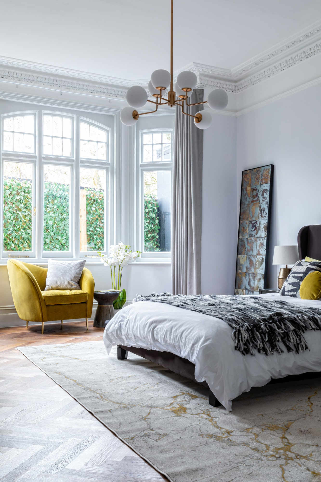 Interior design photograph of a bedroom with light blue walls, brown velvet bed, yellow armchair and beautiful ceiling lighting
