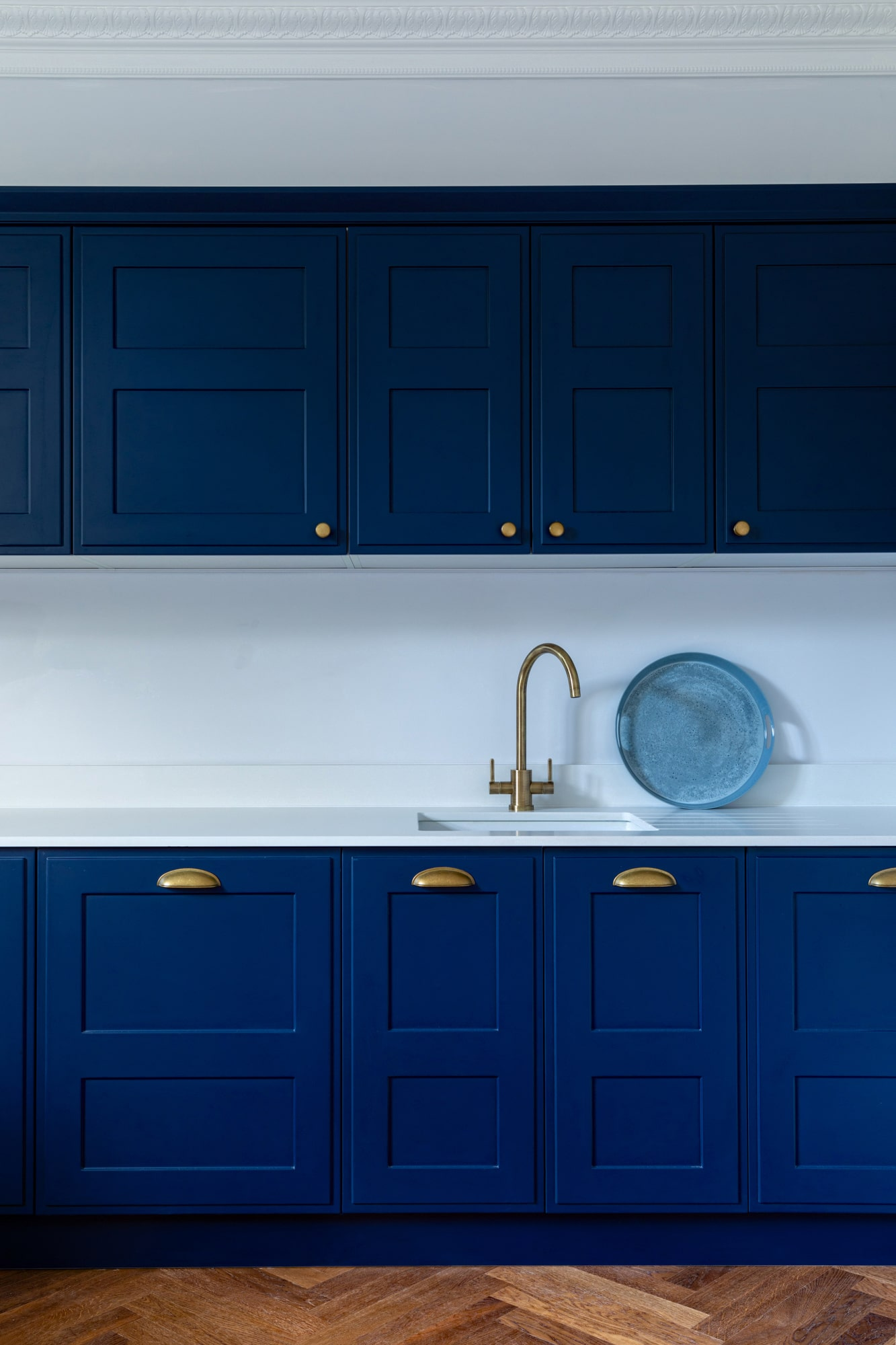 Interior design photograph of a navy blue kitchen with golden tap
