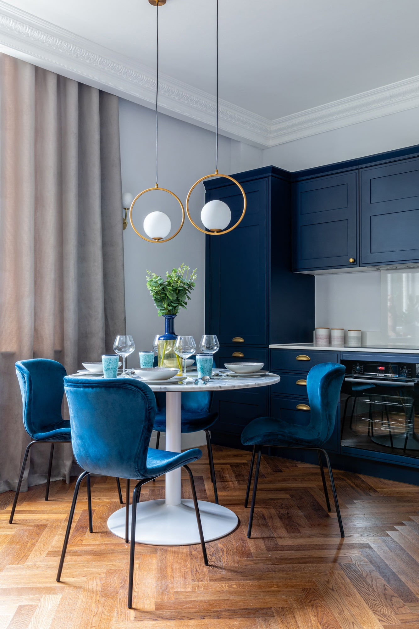 Interior design photograph of a navy blue kitchen, marble table and dark blue velvet chairs