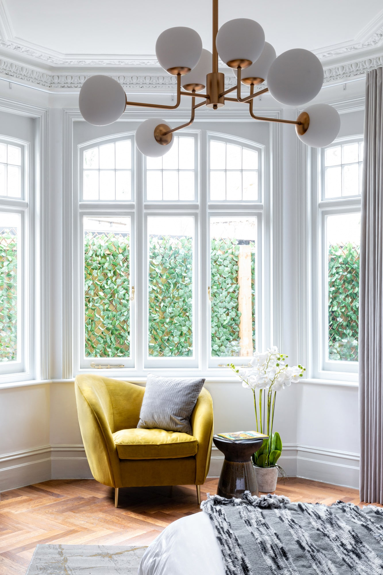 Interior close up photo of a bedroom: big victorian window, yellow armchair with a pillow and a beautiful ceiling lighting