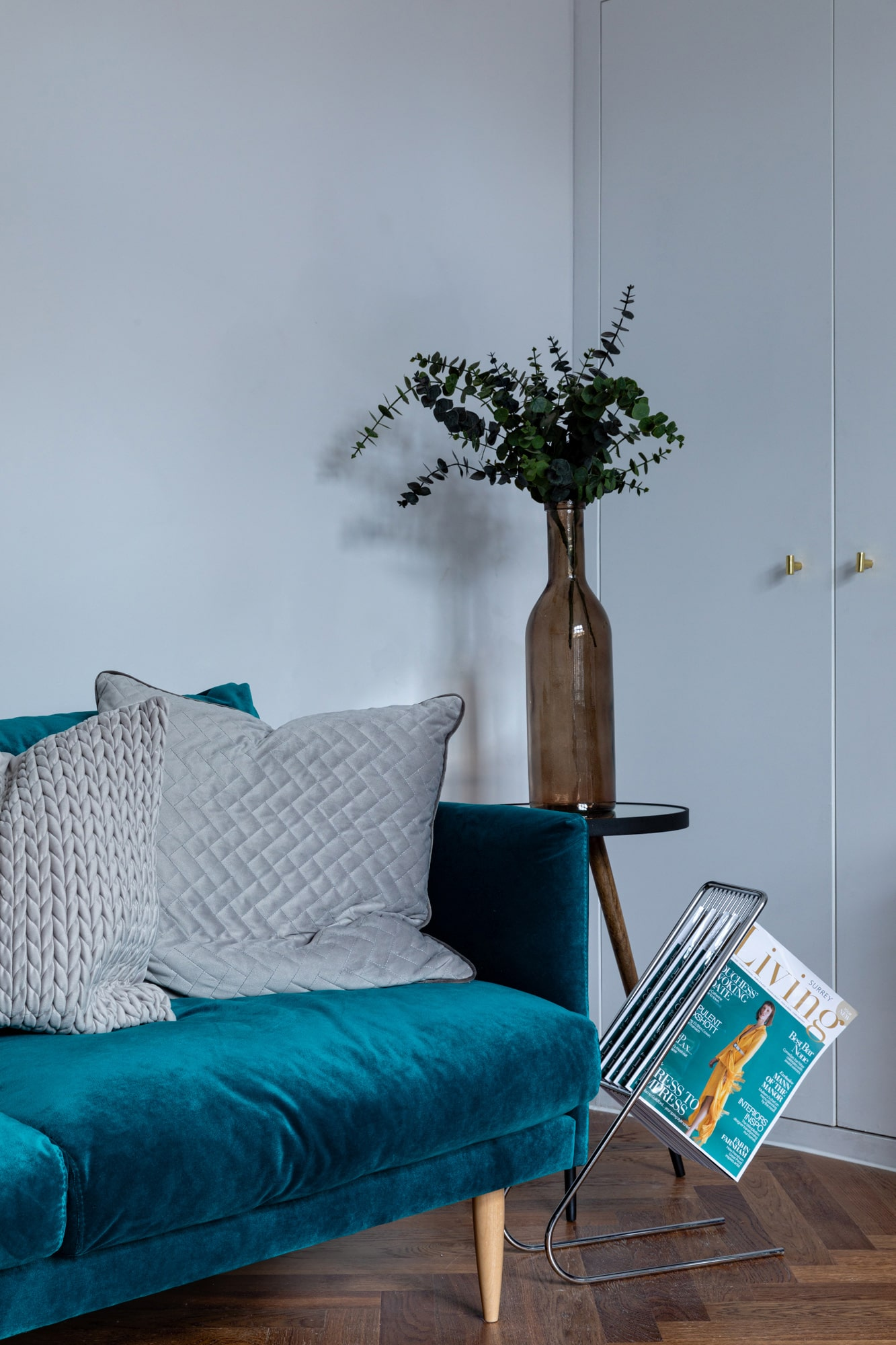 Interior photo close up of a teal blue sofa with two pillows and a side table with a vase