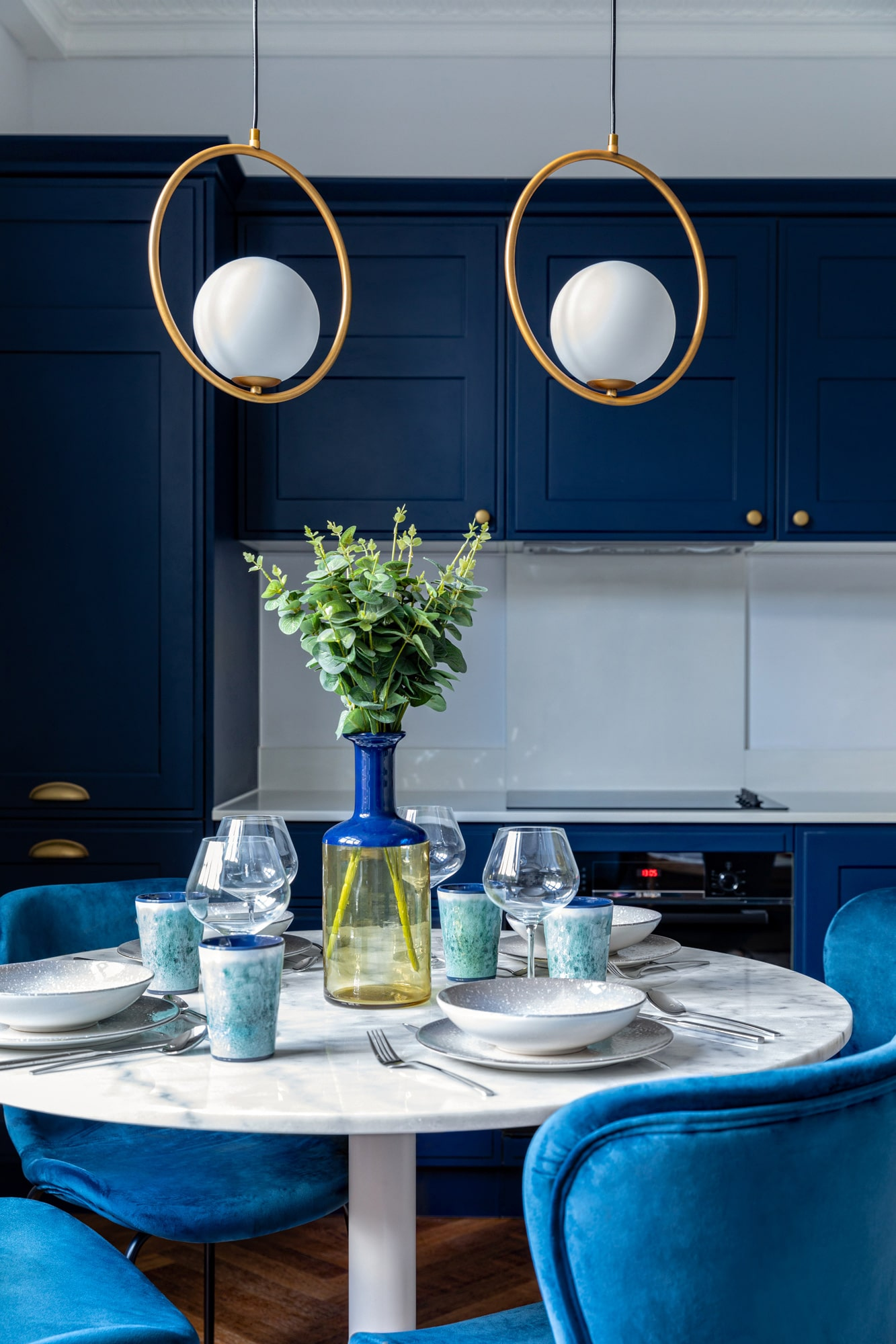 Interior close up photo of a navy blue kitchen, marble table and dark blue velvet chairs