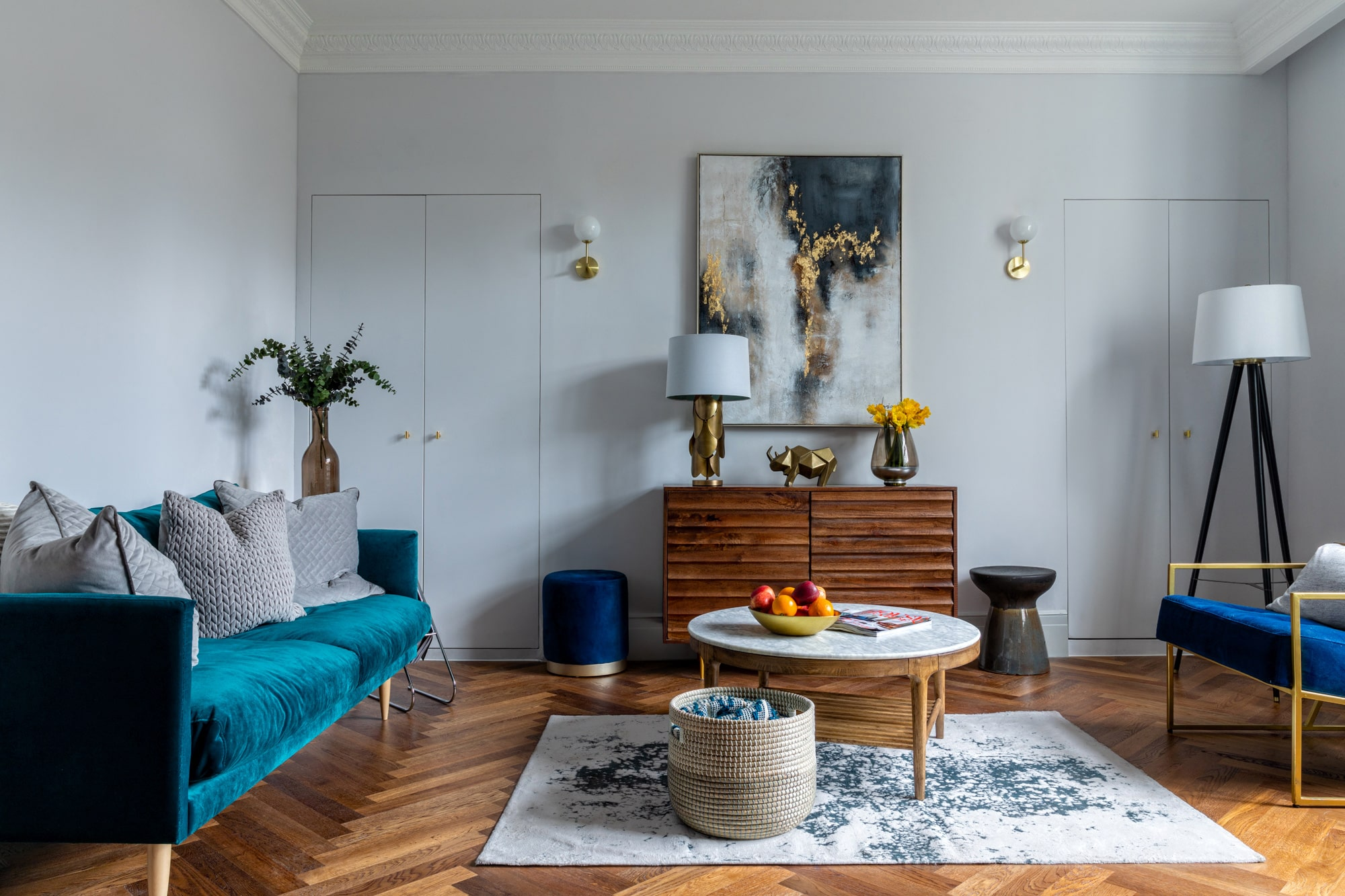Overview interior photograph of a living room with a wooden cabinet, abstract painting, wooden table with marble top, teal blue sofa and abstract painting