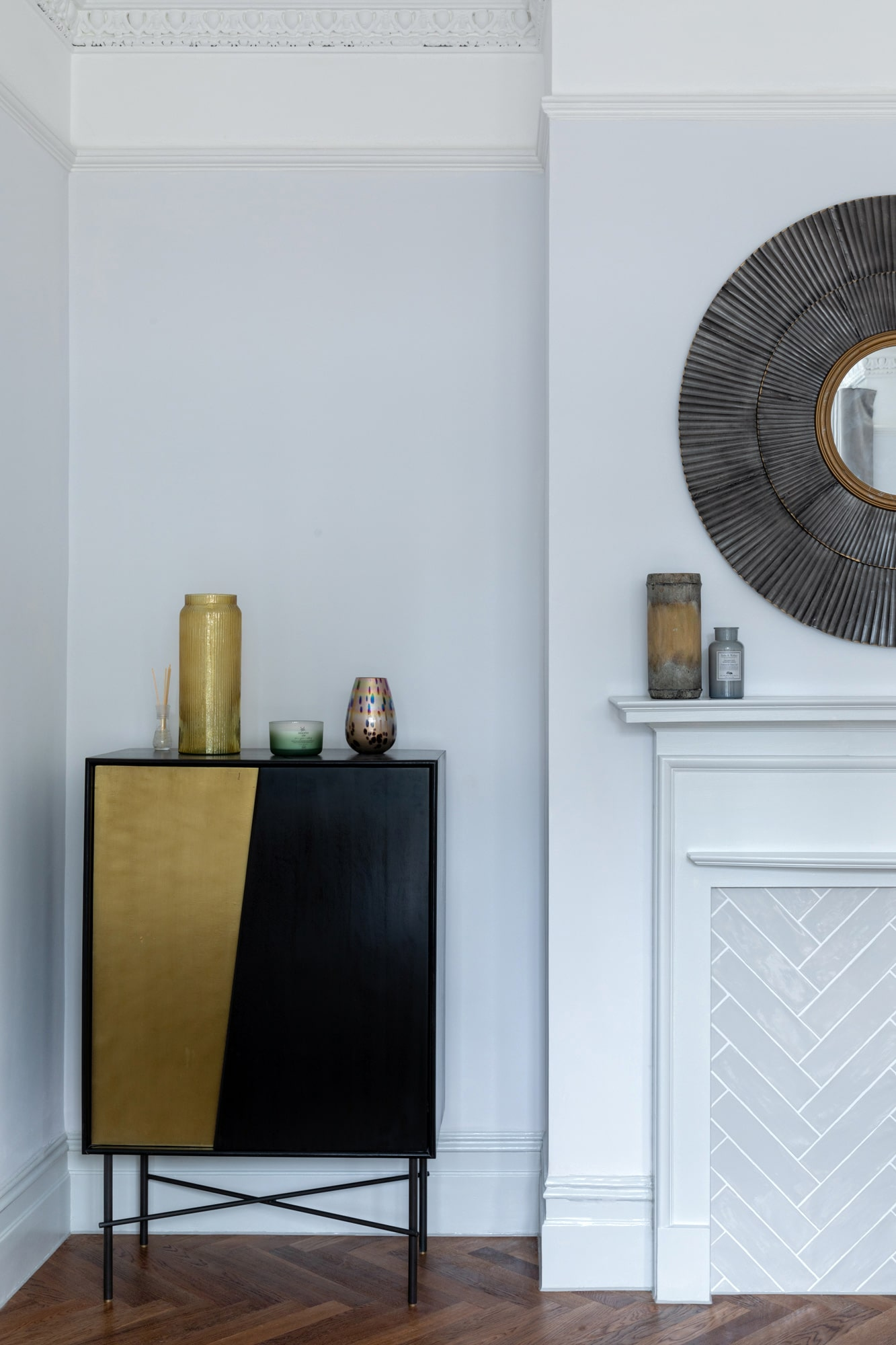 Interior design photography: bedroom with light blue walls, black and golden cabinet yellow vases on it and round mirror above a fireplace
