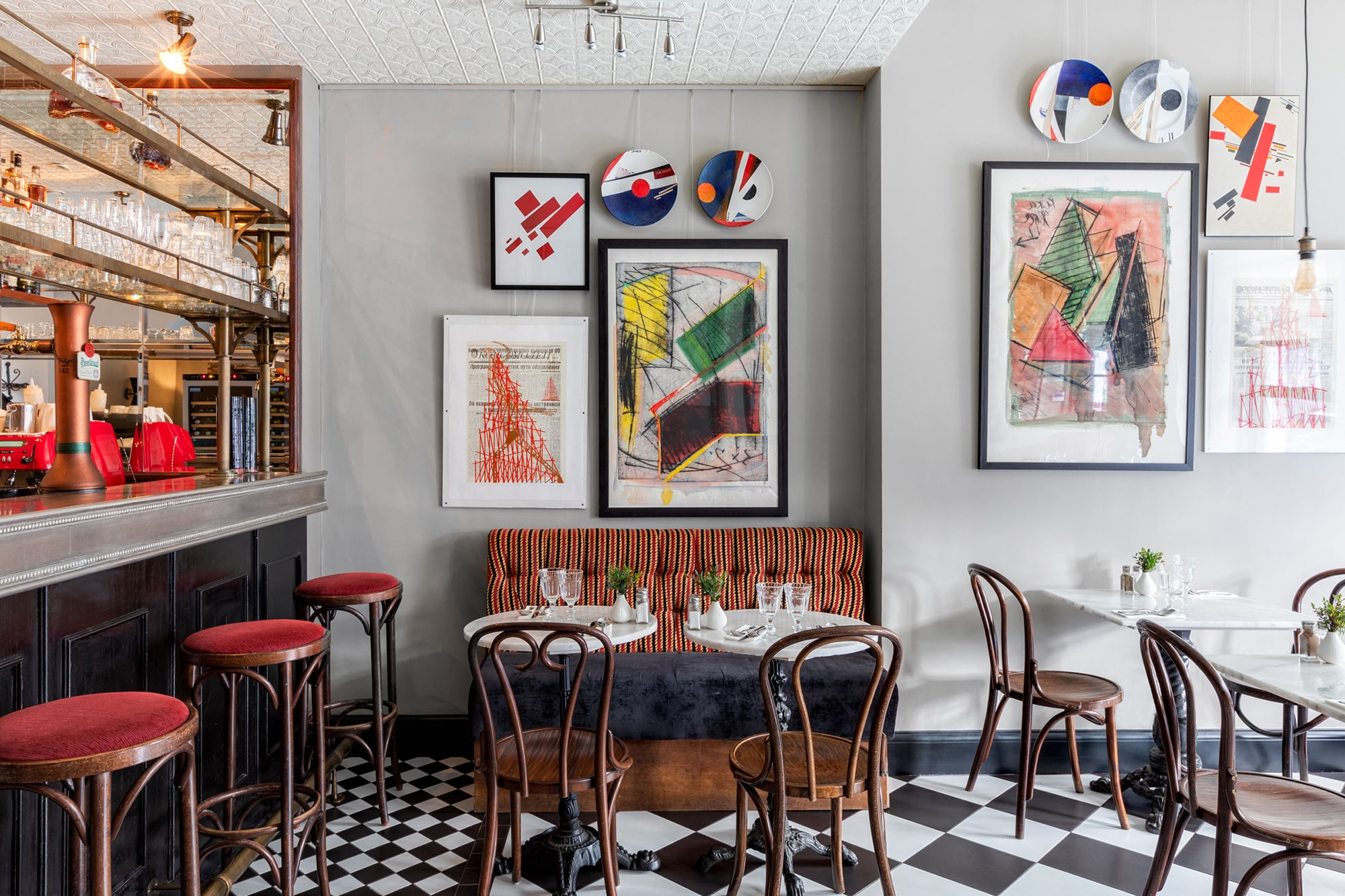 Interior shot of a restaurant; modern art prints on grey walls; corner of the bar and bar stools; tables with marble tops and wooden chairs