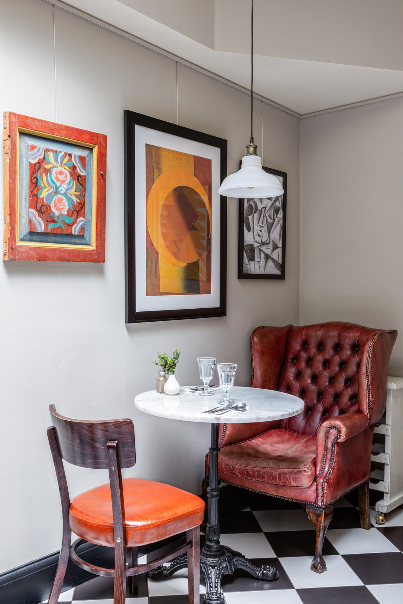 Interior photo of a Russian restaurant: modern art prints; round table, a leather armchair and a wooden chair