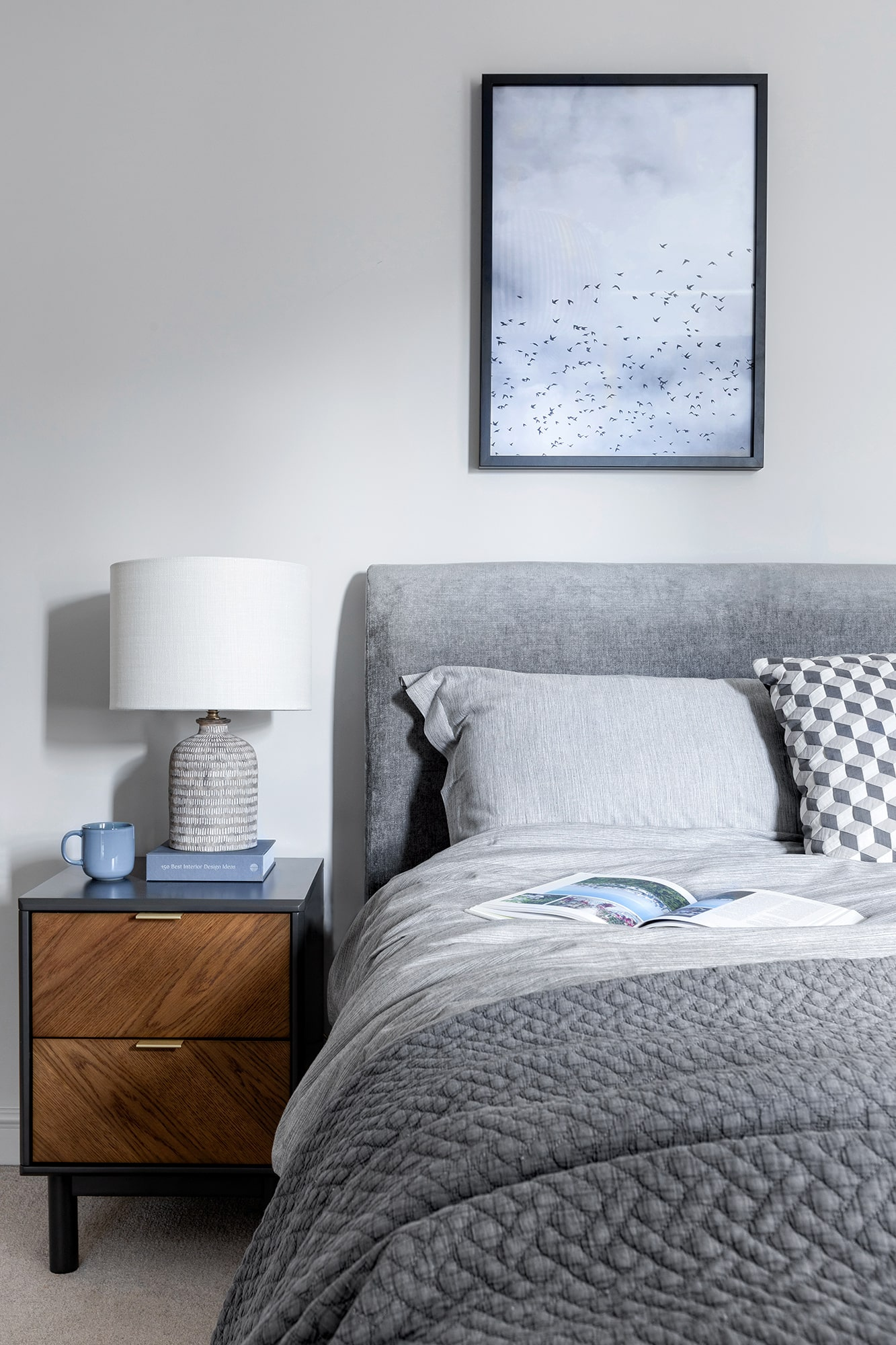 interior design of a bedroom: light grey walls; grey bed with grey bedding; brown wooden bedside table; white lamp; blue poster with small birds