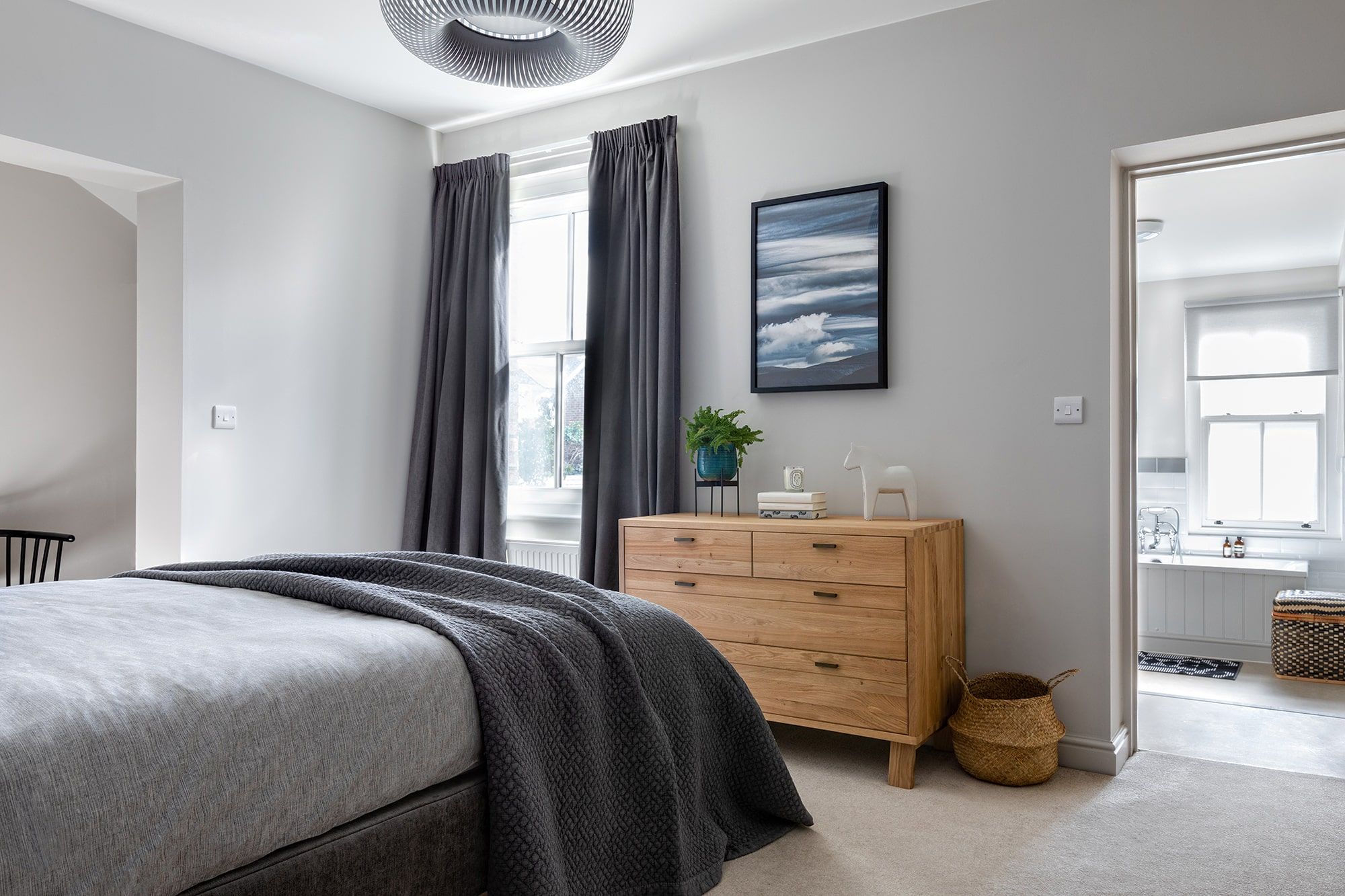 interior design photo: bedroom with light grey walls; grey ceiling light; bed with grey bedding; chest of drawers; abstract blue poster on the wall