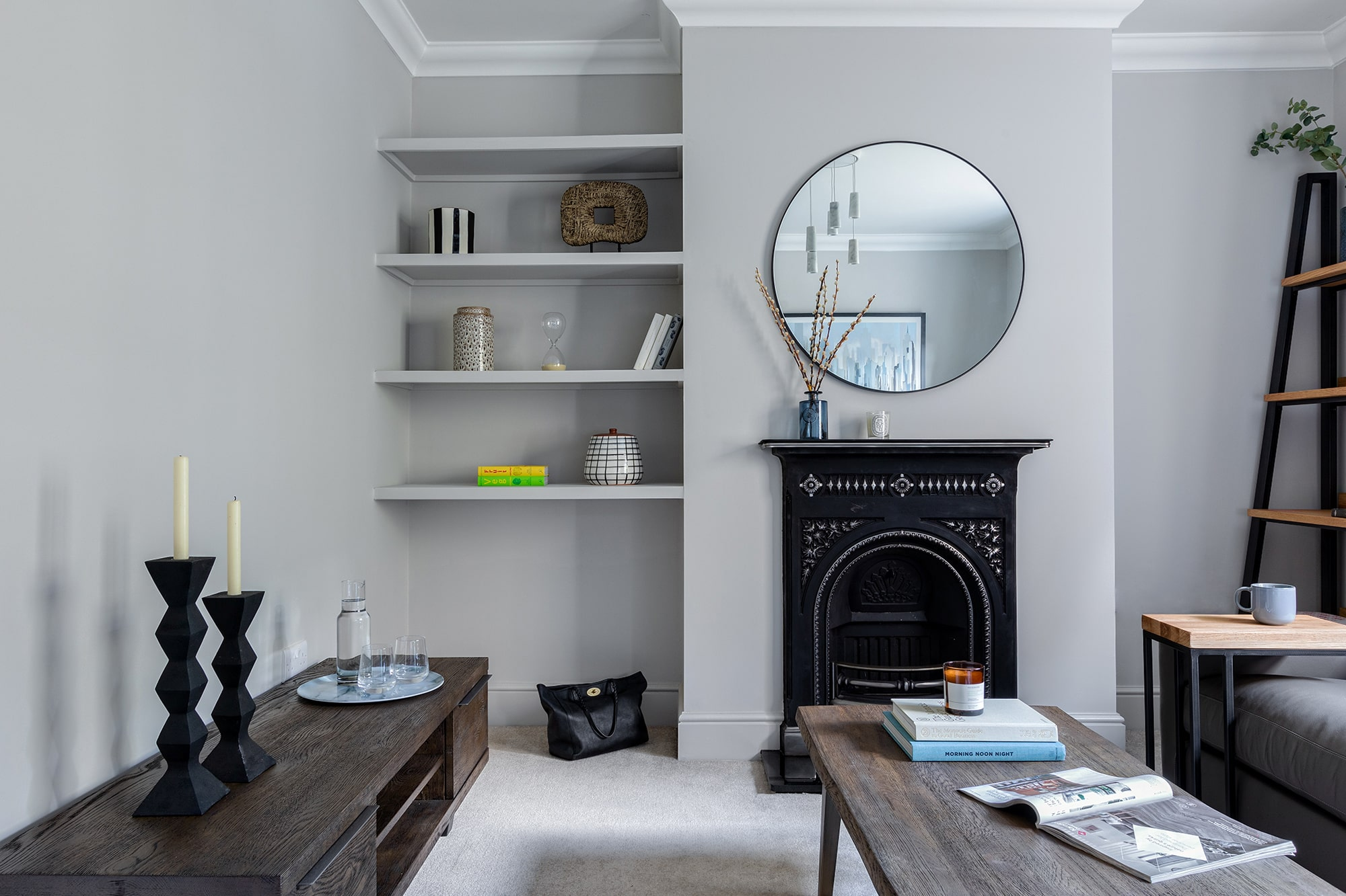 interior design photo: living room with grey walls; built in shelves; black fireplace; round mirror; wooden coffee table; tv stand