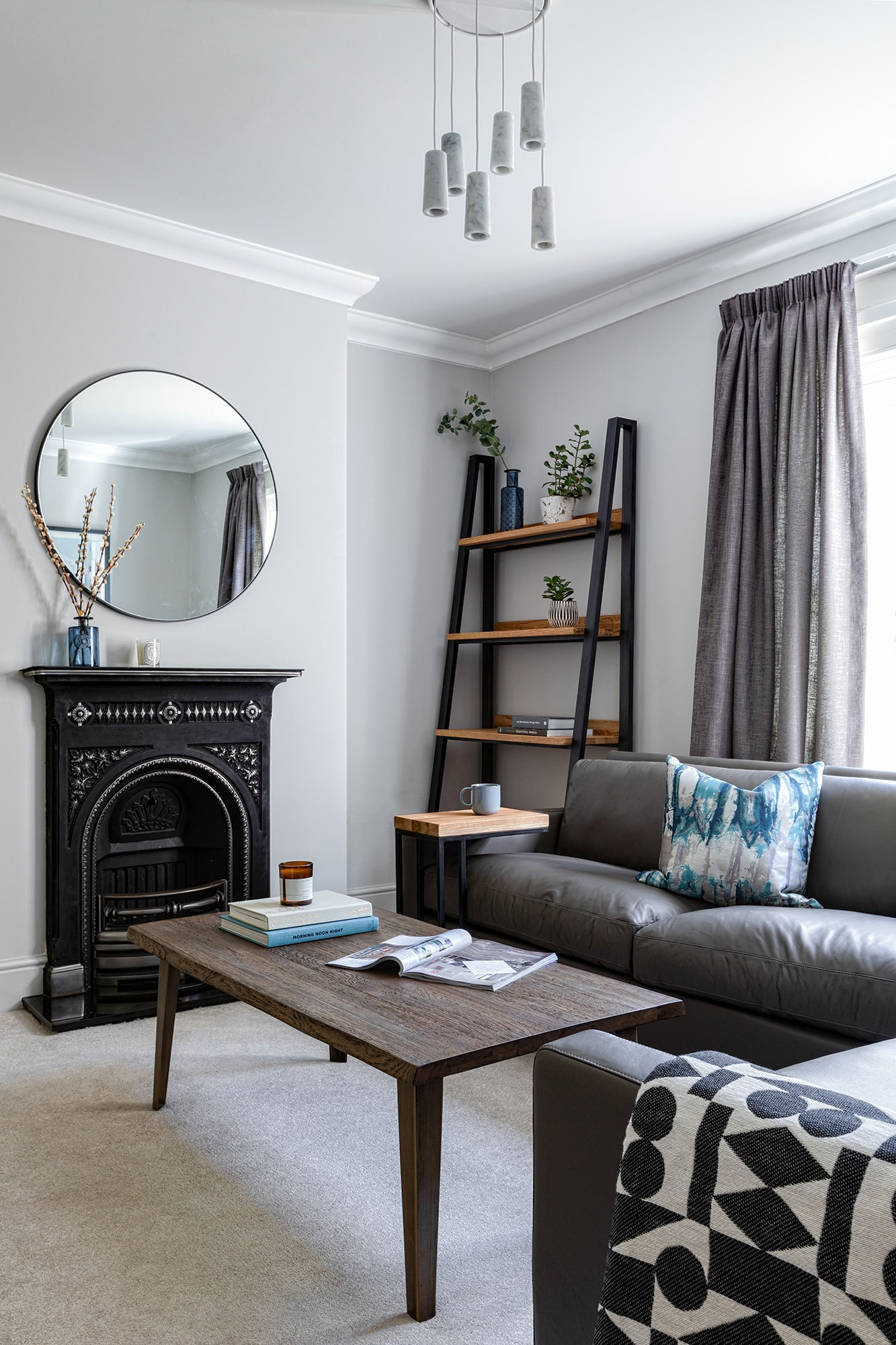interior shot: living room with grey walls; grey sofa, blue cushion; ladder shelving unit; fireplace and round mirror