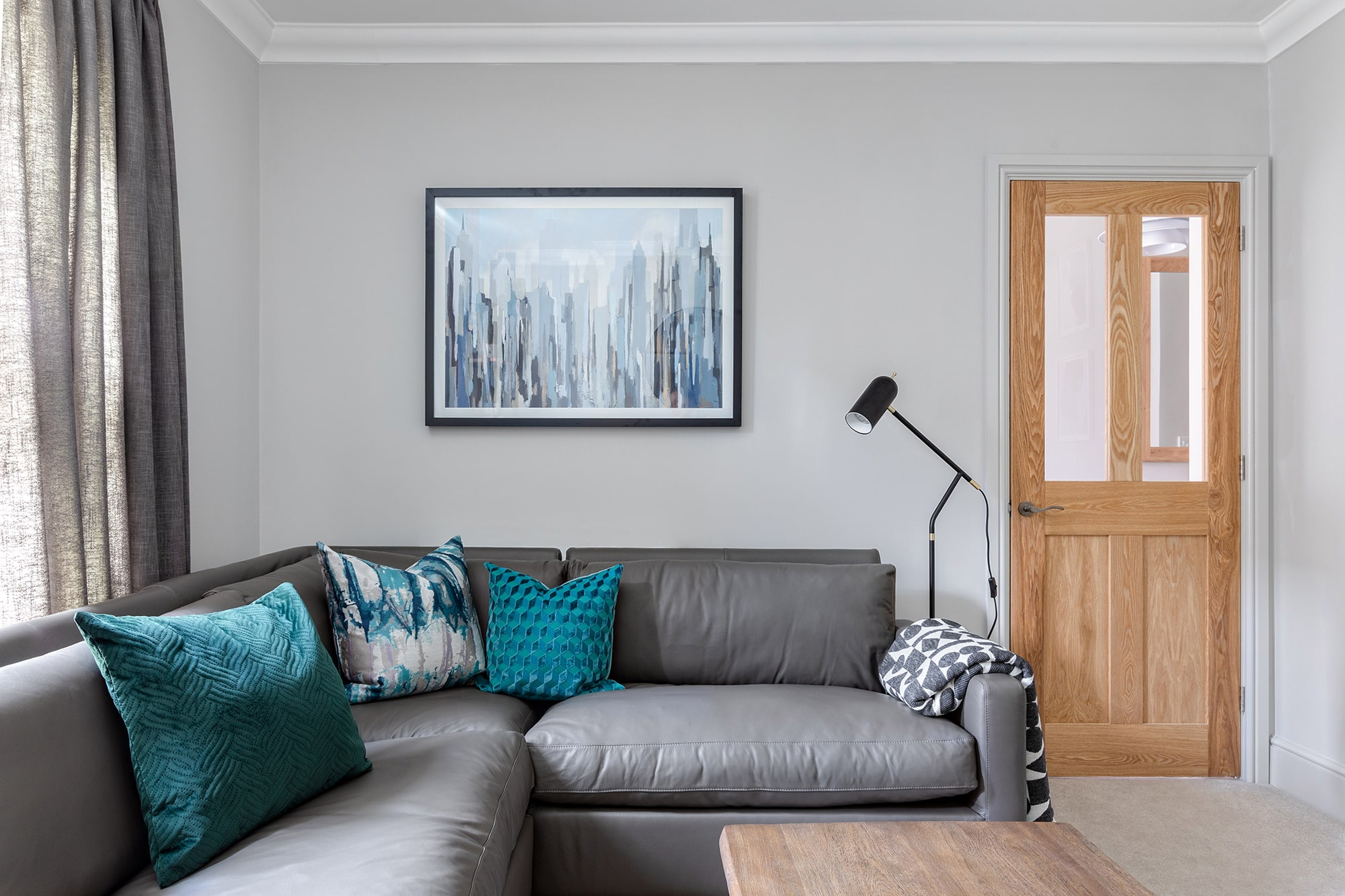 Interior design photo: living room with grey walls, abstract blue art; grey sofa with teal cushions; black standing lamp