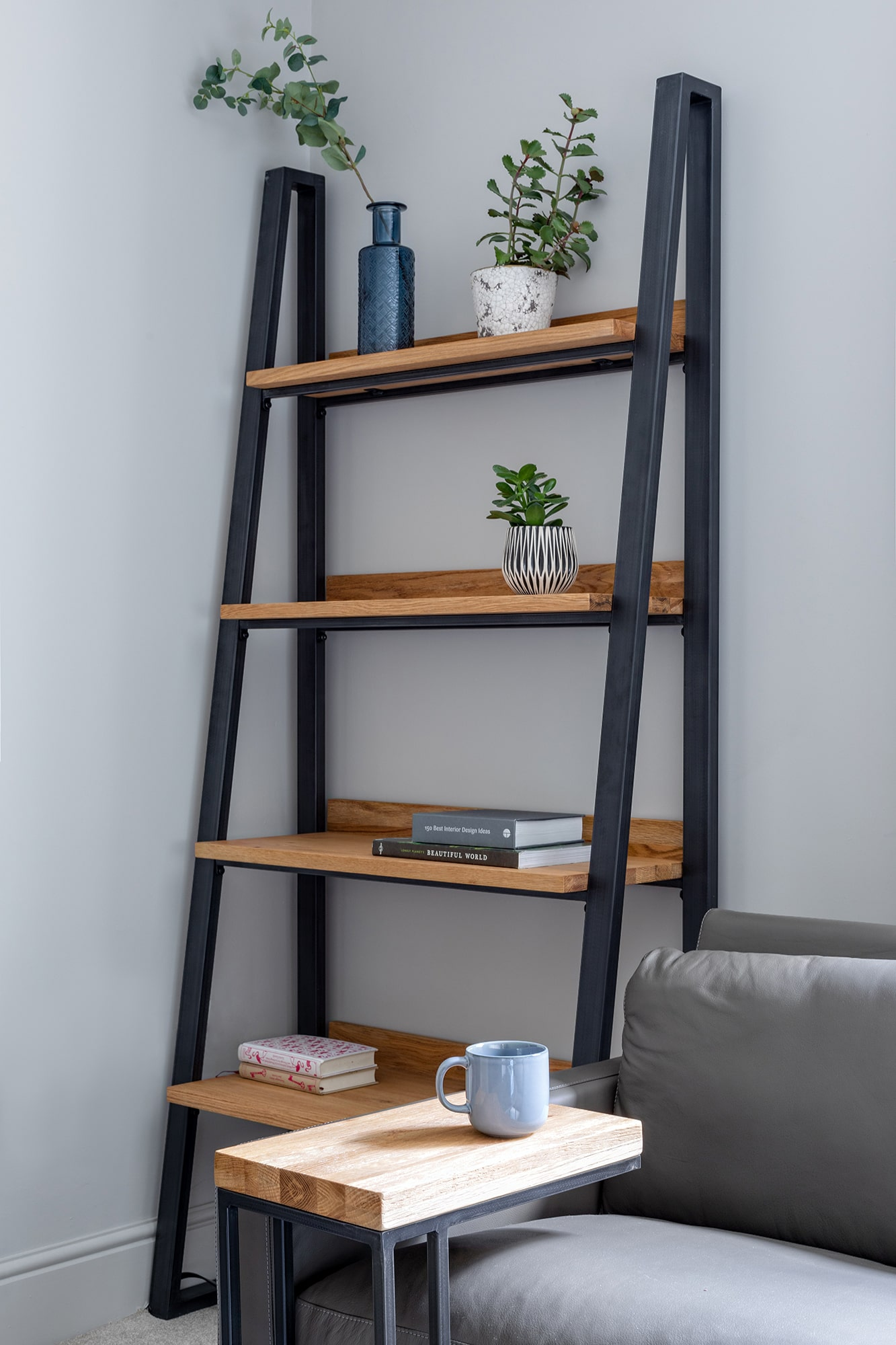 interior detail photo: living room, ladder shelving unit with decor accessories, corner of a sofa