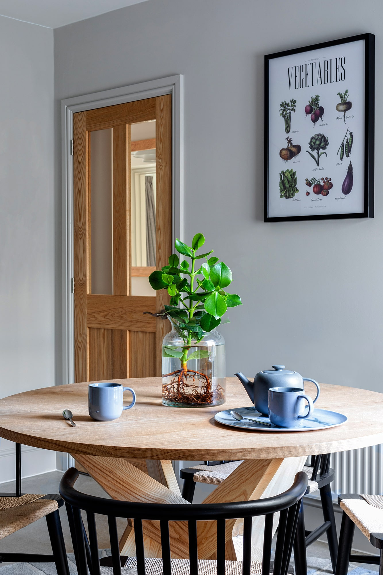 dining area with light grey walls; round wooden table; round black chairs; blue china on top