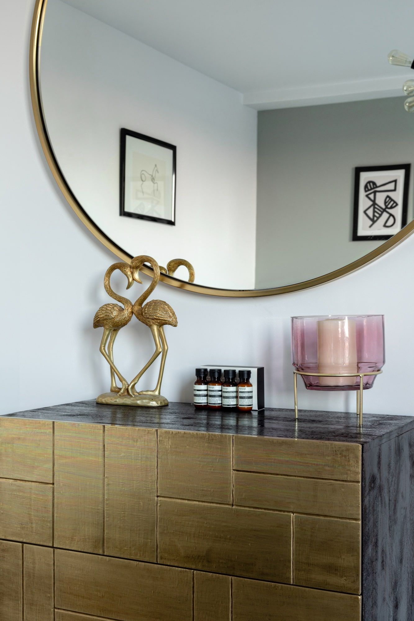 interior detail photo: gold chest of drawers from Swoon, round mirror, accessories on top
