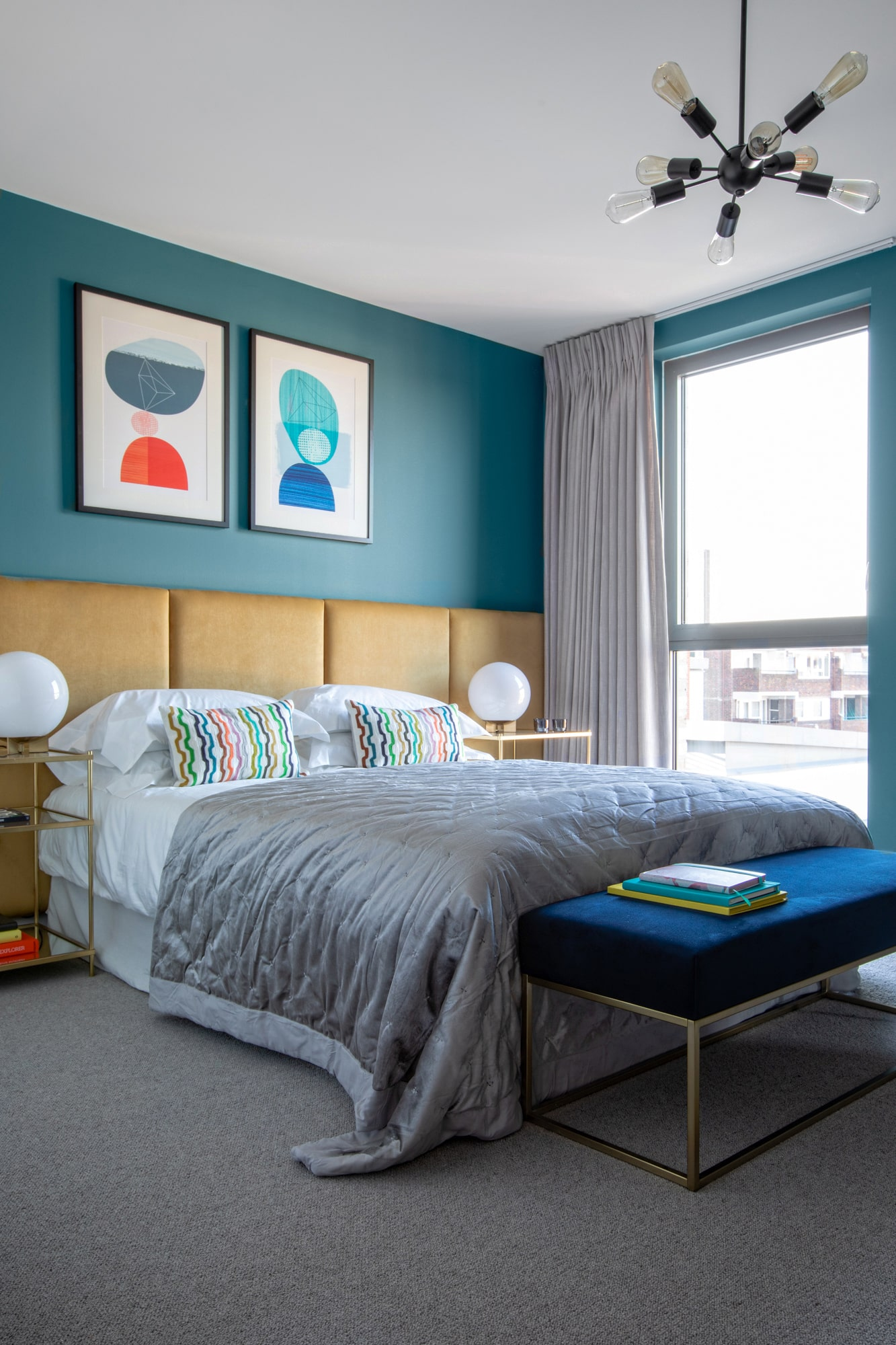 Interior design photo: bedrooms with teal walls; yellow bed; abstract art; blue velvet bench