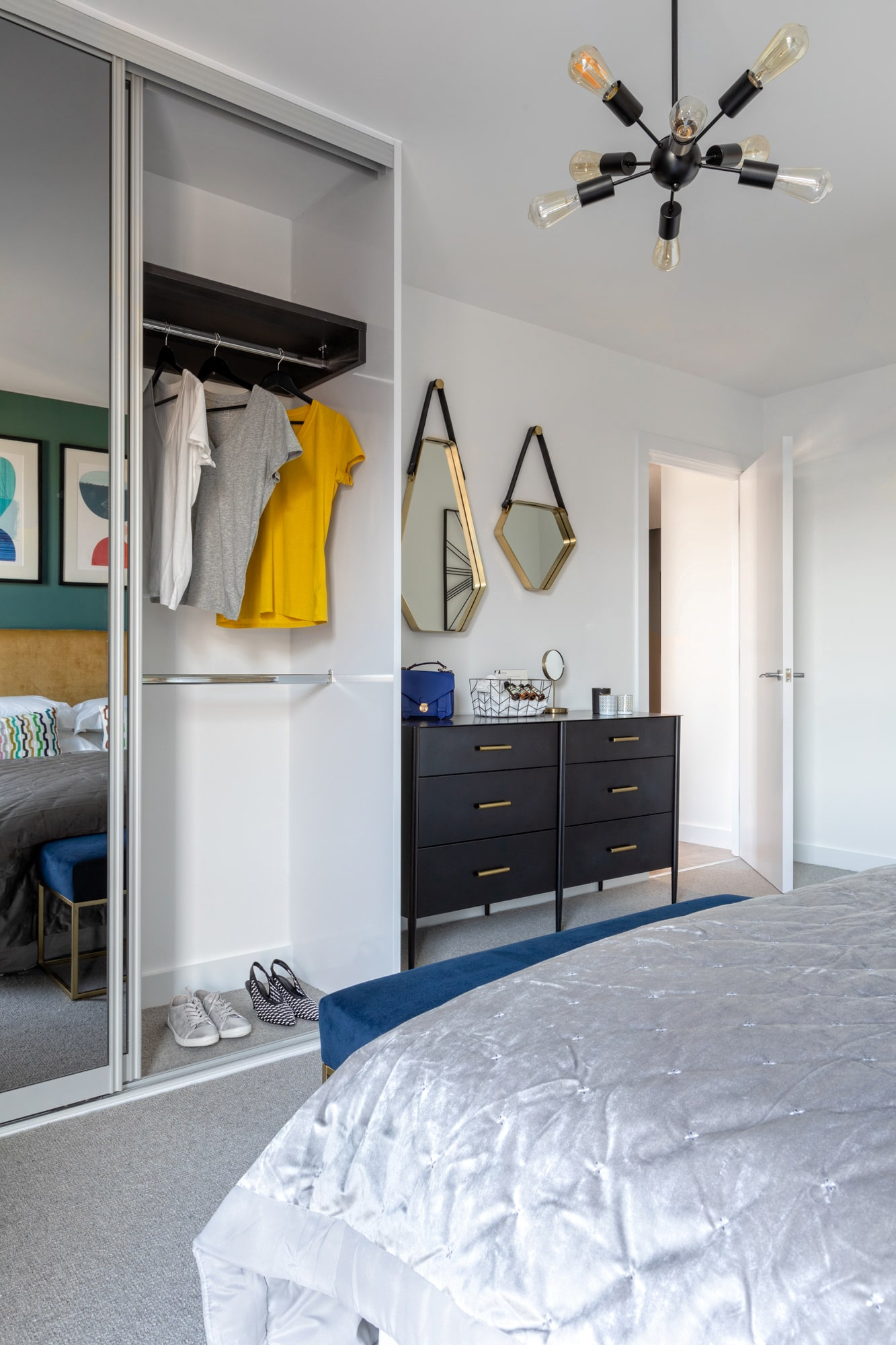 interior design photo: chest of drawers with triangle mirrors above; open wardrobe with some cloths
