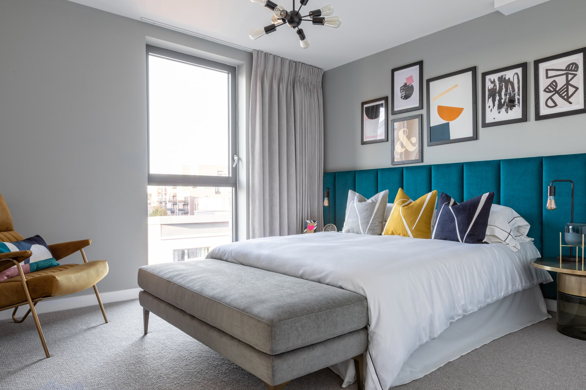 interior photo of a bedroom: light grey walls; art wall gallery; teal bed, grey, blue and yellow cushions; round bedside table; brown armchair