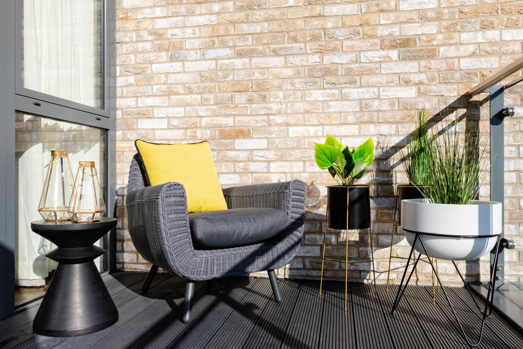 balcony decor photo: an armchair with yellow cushion, a round table, two plants on stands