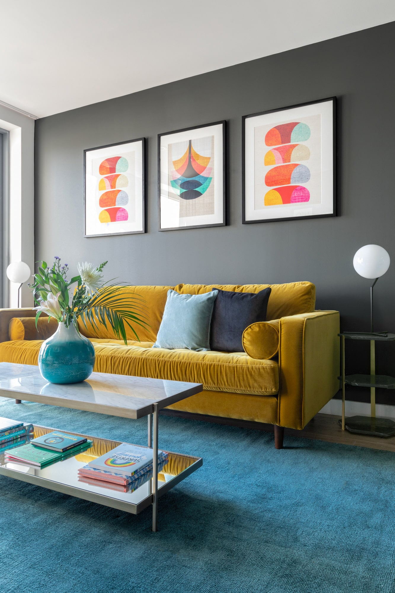 Interior design photography: living room with dark grey walls, yellow velvet sofa, marble coffee table, abstract art on the wall