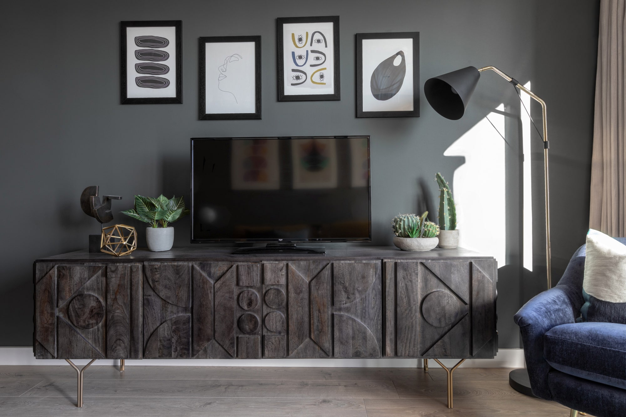 interior photo: living room with dark grey walls; wooden tv stand; tv; wall art gallery