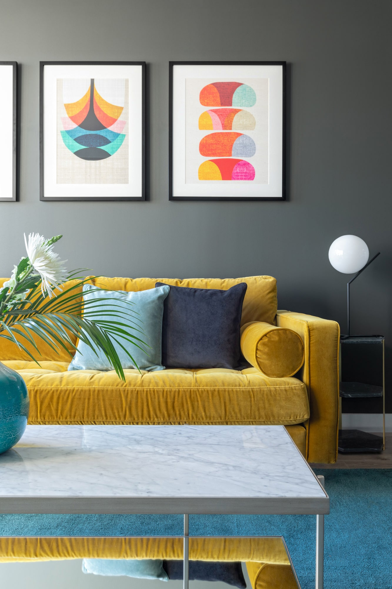 interior design photo of a living room: dark grey walls; yellow velvet sofa, marble coffee table; side table with a lamp