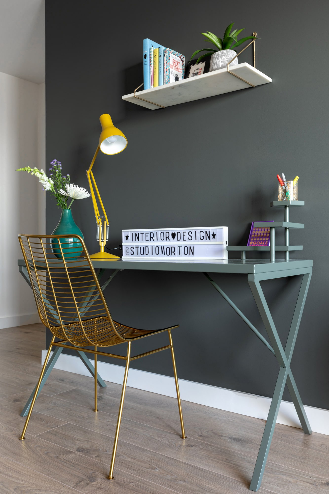 interior photo: dark grey walls; green desk with yellow table lamp; gold metal chair