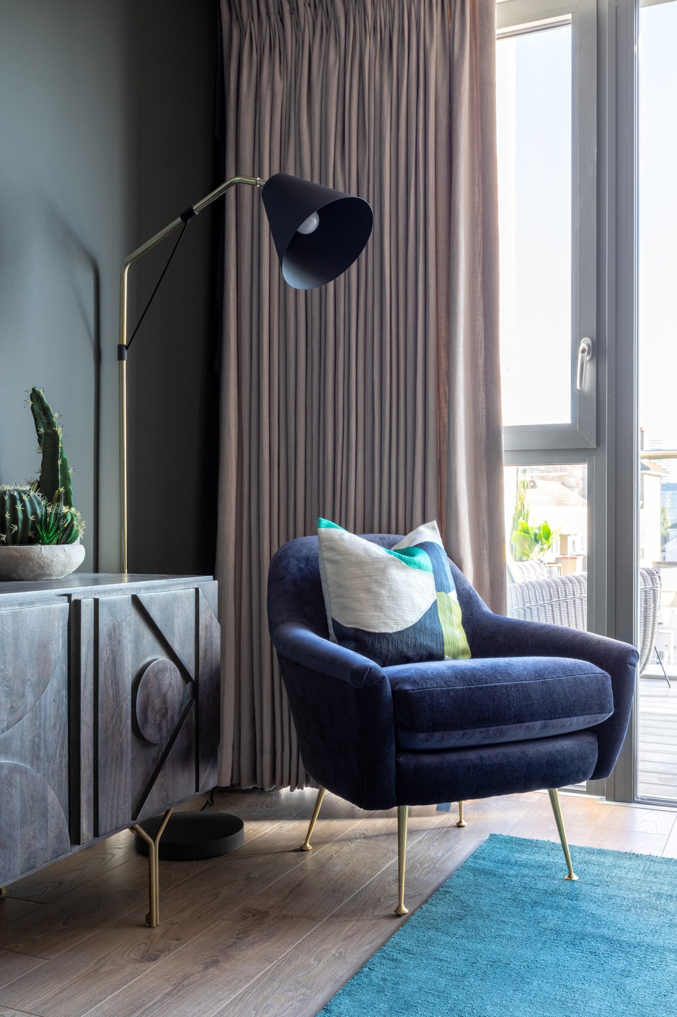 interior design photo: blue velvet armchair next to the window; wooden tv stand