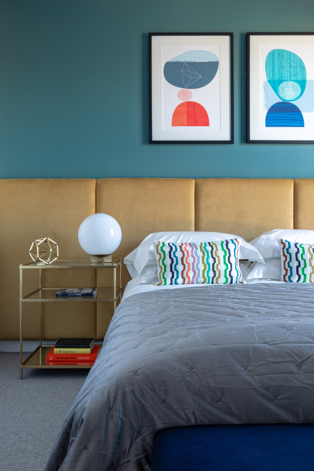 Interior design photo: bedrooms with teal walls; yellow bed; abstract art; glass bedside table