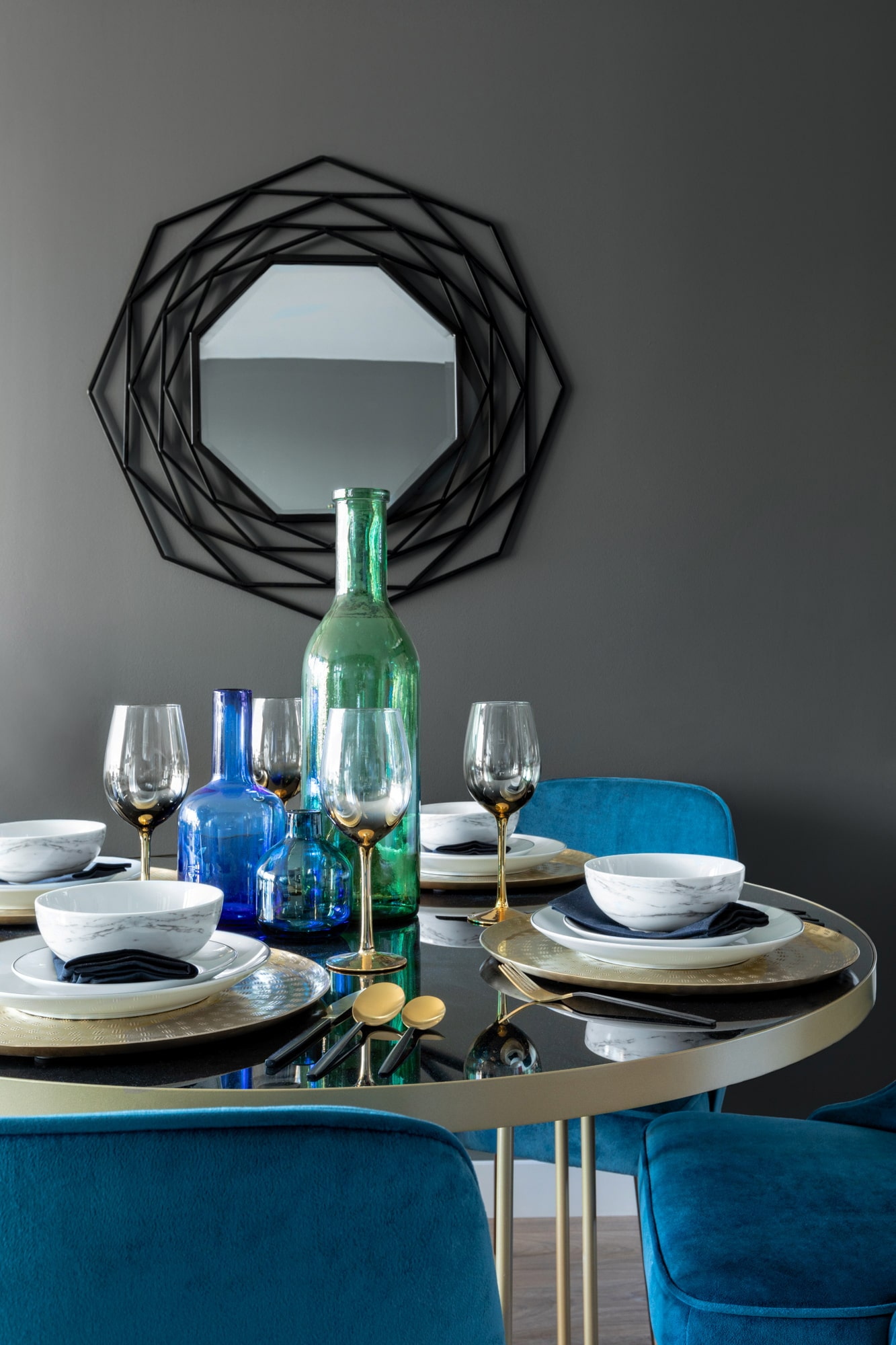 interior detail photo: living room with dark grey walls; round table with blue chairs; round glass table; plates and blue and green bottle
