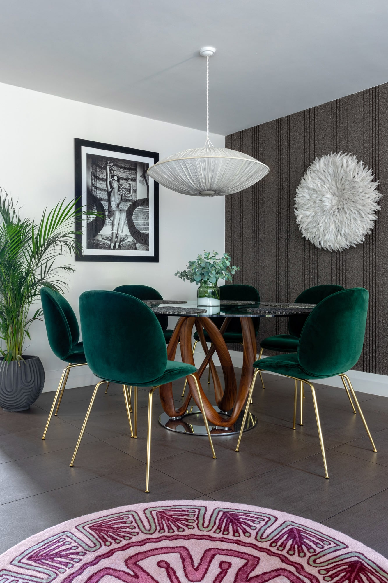 Interior design photo: living room: round table with a glass top, green velvet chairs; black and white photo of a woman on the wall; grey feature wall with hanging round white accessory made of feathers