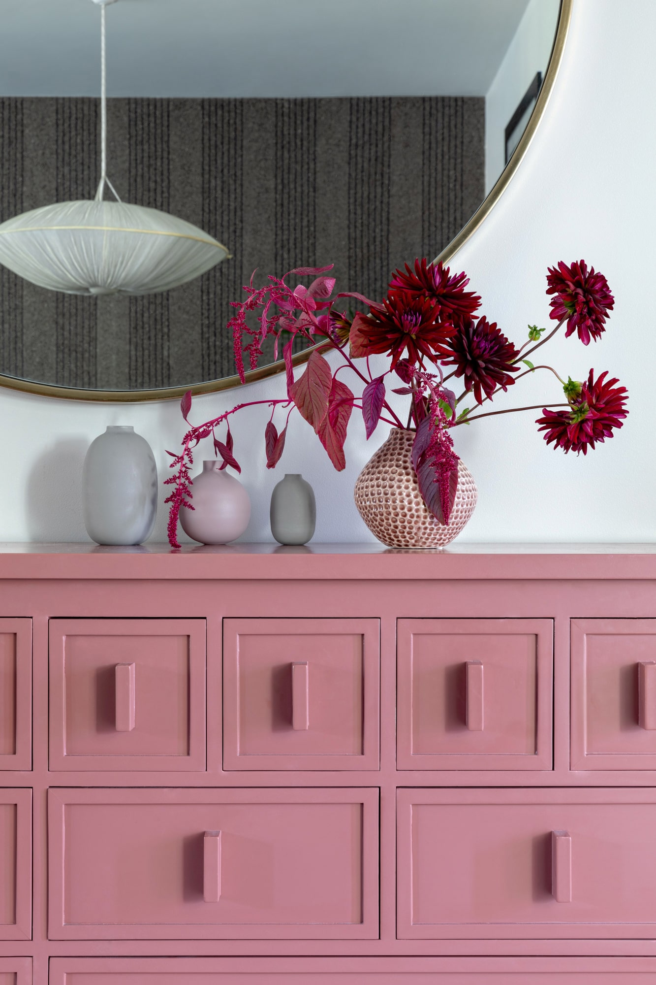 interior detail shot: pink cabinet, burgundy flowers, mirror with a ceiling lamp reflection