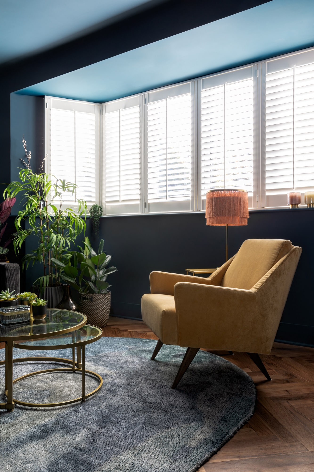 dark blue tv room with many plants, glass round coffee table and yellow armchair