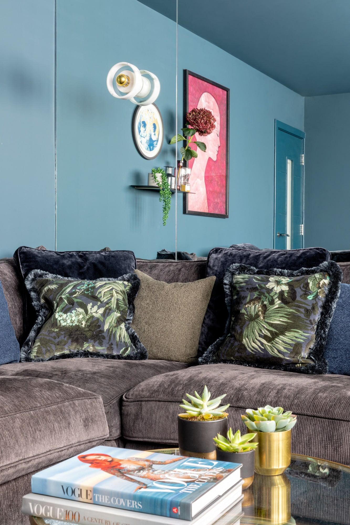 dark blue tv room detail shot, brown velvet sofa, colourful cushions, glass round coffee table with succulents and fashion books on top
