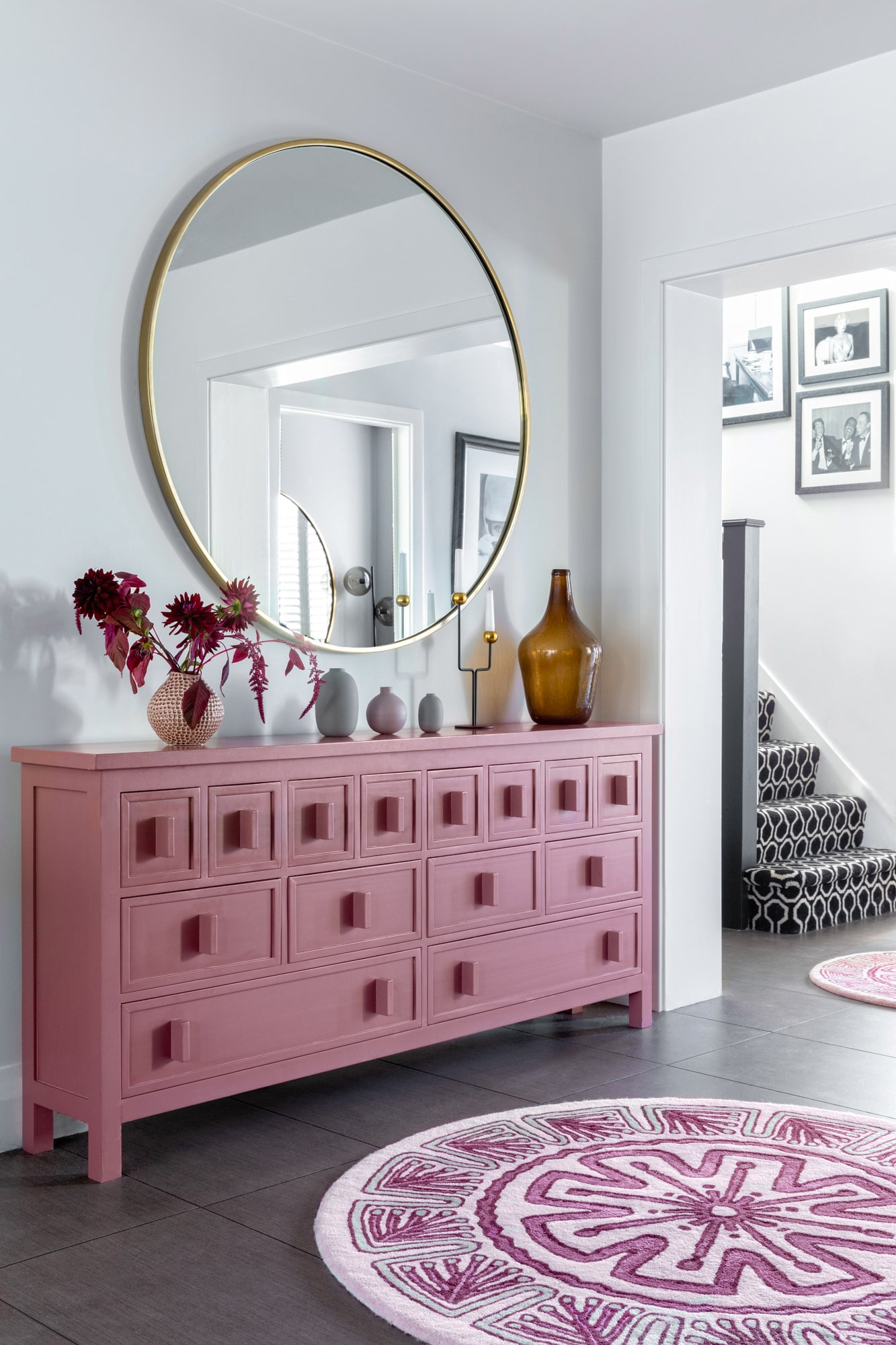 Interior photo of a living room: pink cabinet with accessories on top; pink round rug; round mirror on the wall
