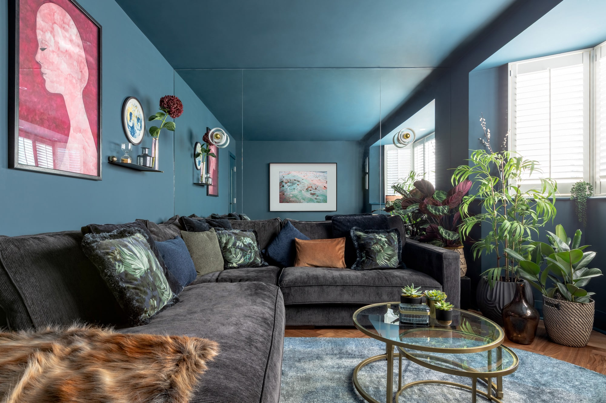 Interior photo: dark blue tv room, brown velvet corner, many plants, round glass table, colourful cushions