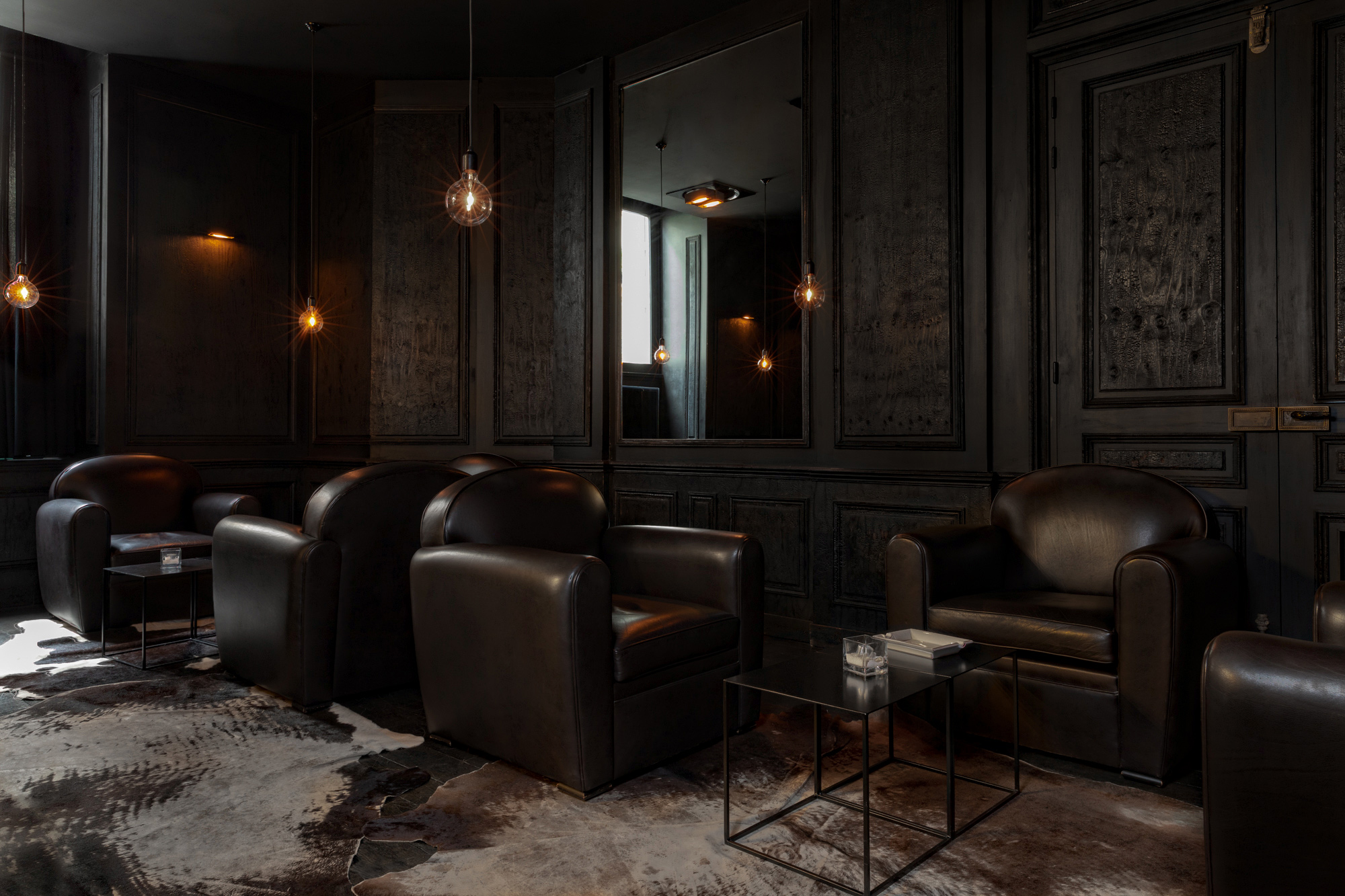 chill room in a hotel: dark brown walls; brown leather armchairs, coffee tables