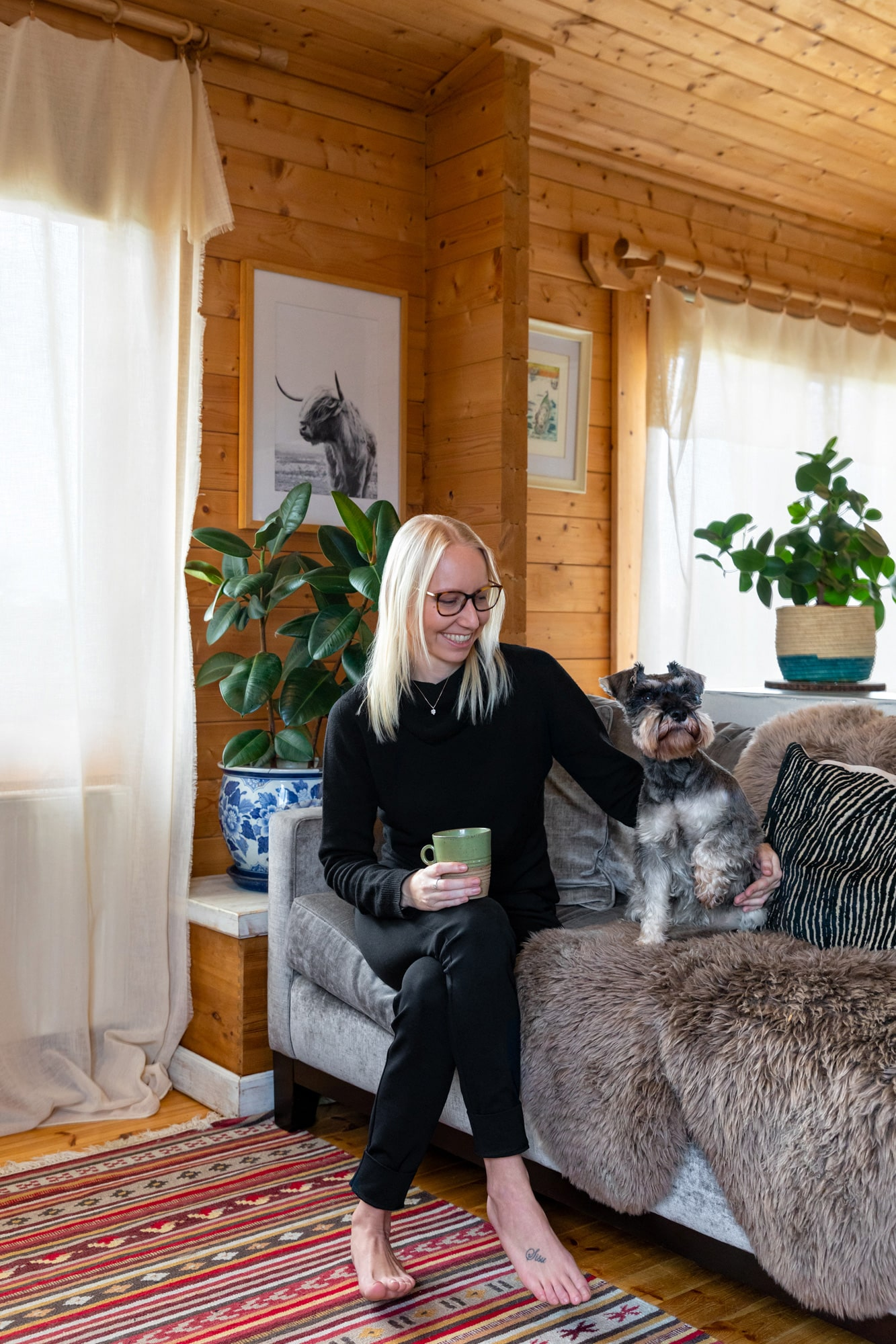 Interior photo in a cabin: a designer witting next to her dog on a sofa