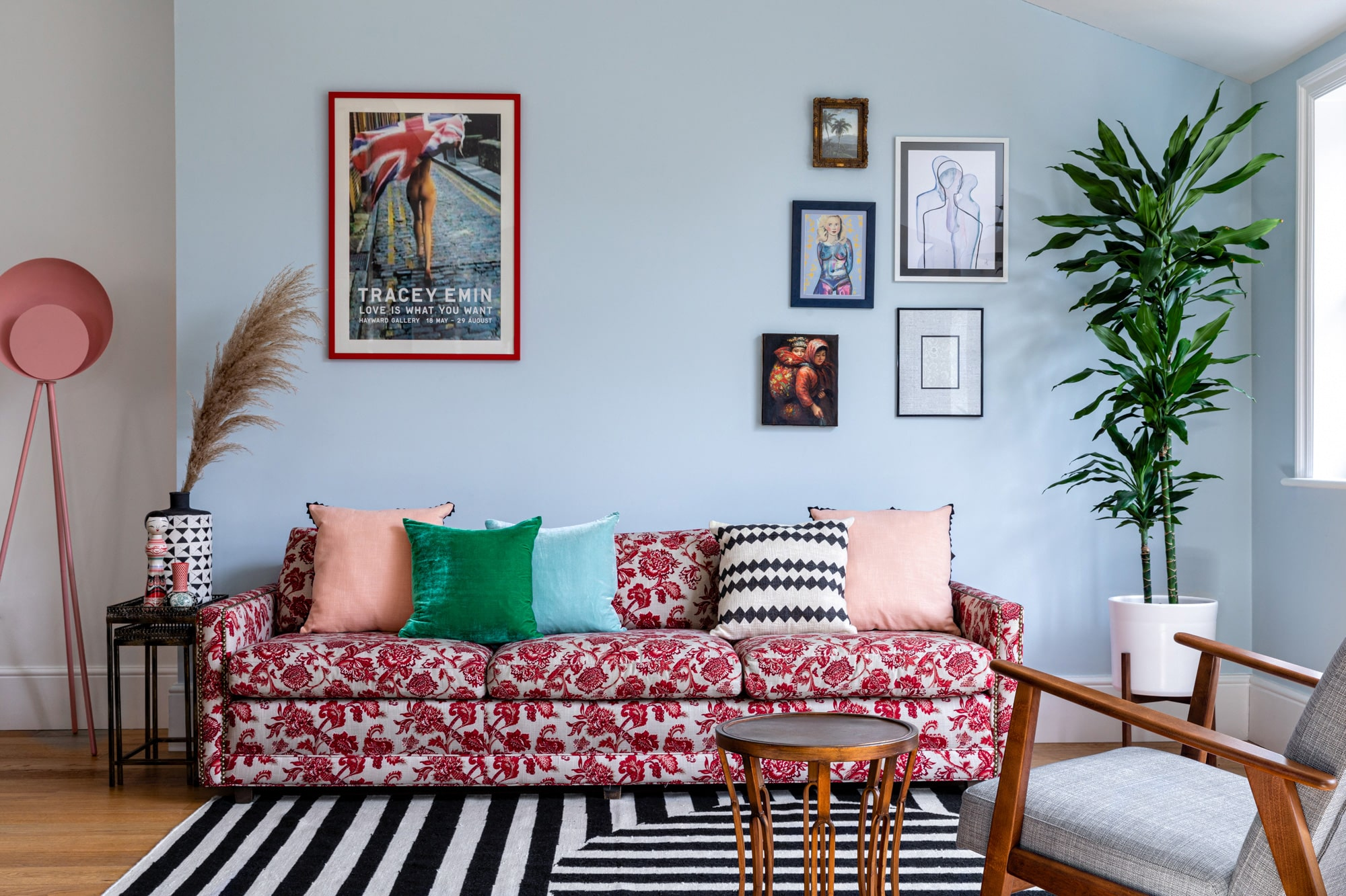 Interior photo of a living room: light blue walls; sofa with red pattern; colourful cushions; Tracey Emin poster; black and white striped rug; wall art gallery