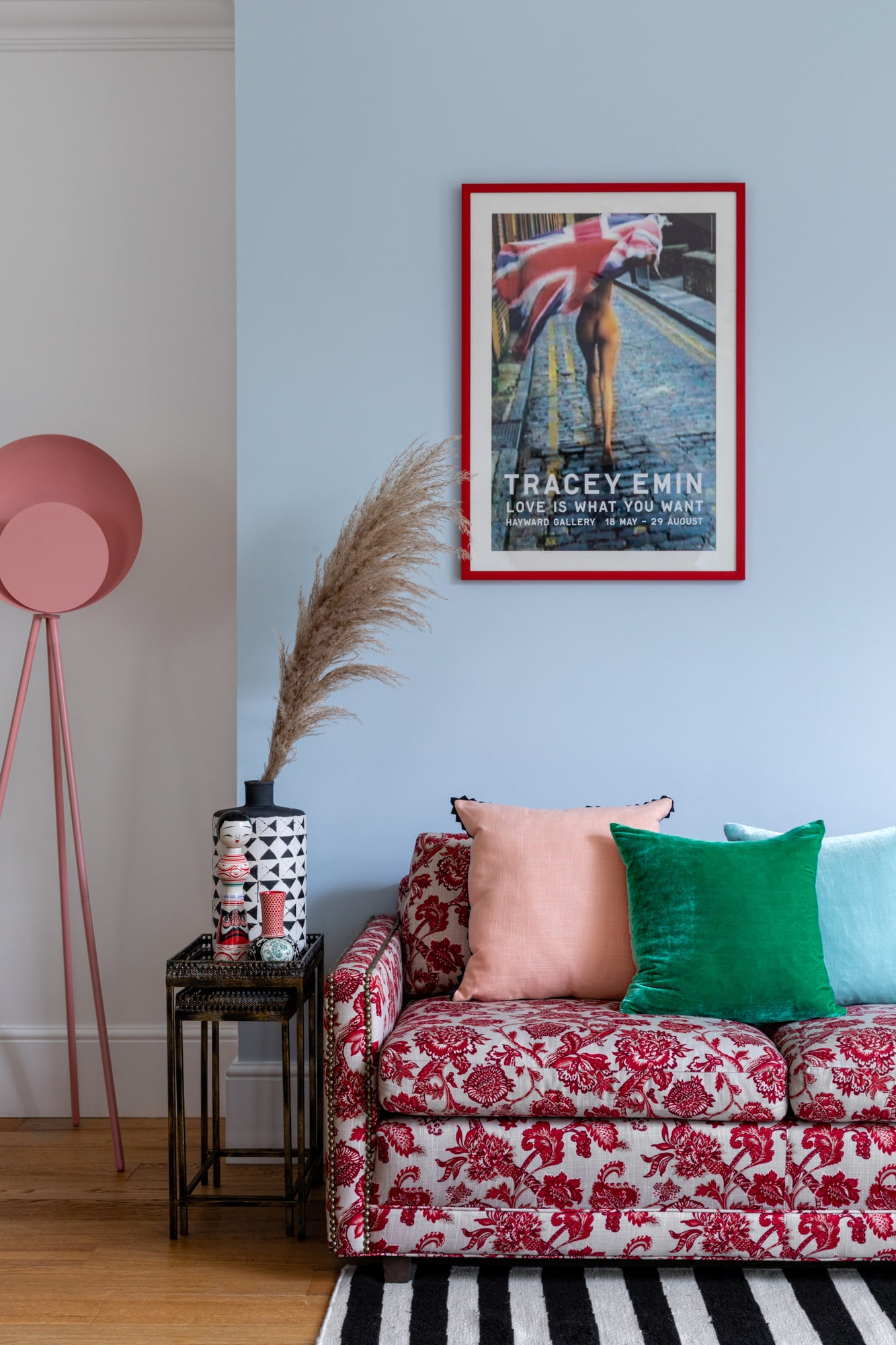 Interior photo of a living room: light blue walls; sofa with red pattern; colourful cushions; Tracey Emin poster; black and white striped rug; side table; astanding pink lamp