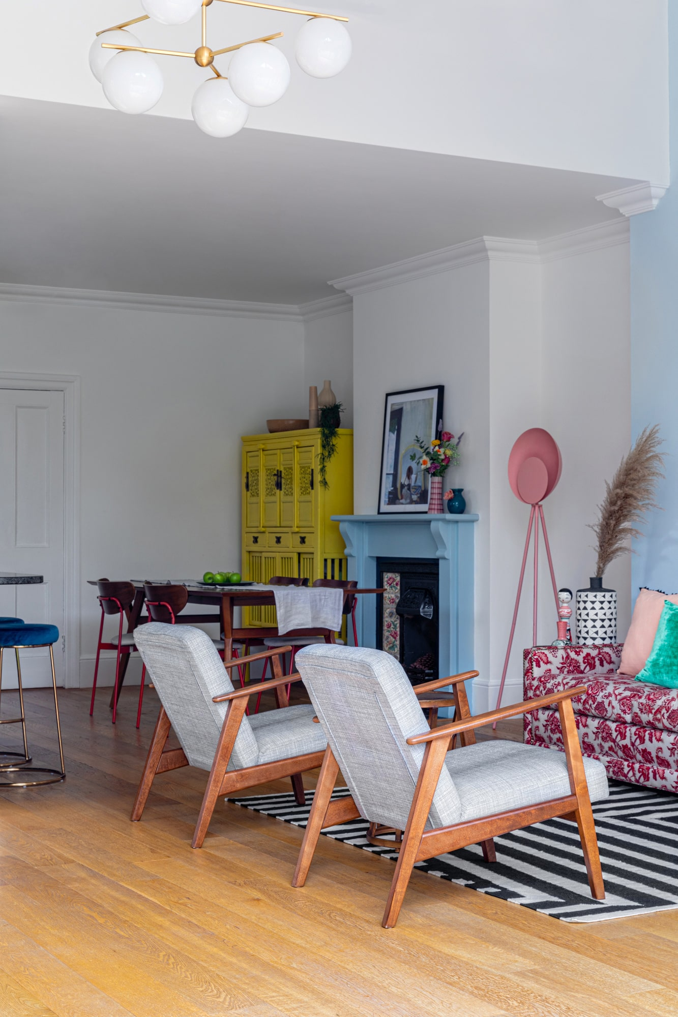 View through living area to dining area; armchairs and a corner of a sofa; blue fireplace; wooden diding table; yellow cabinet