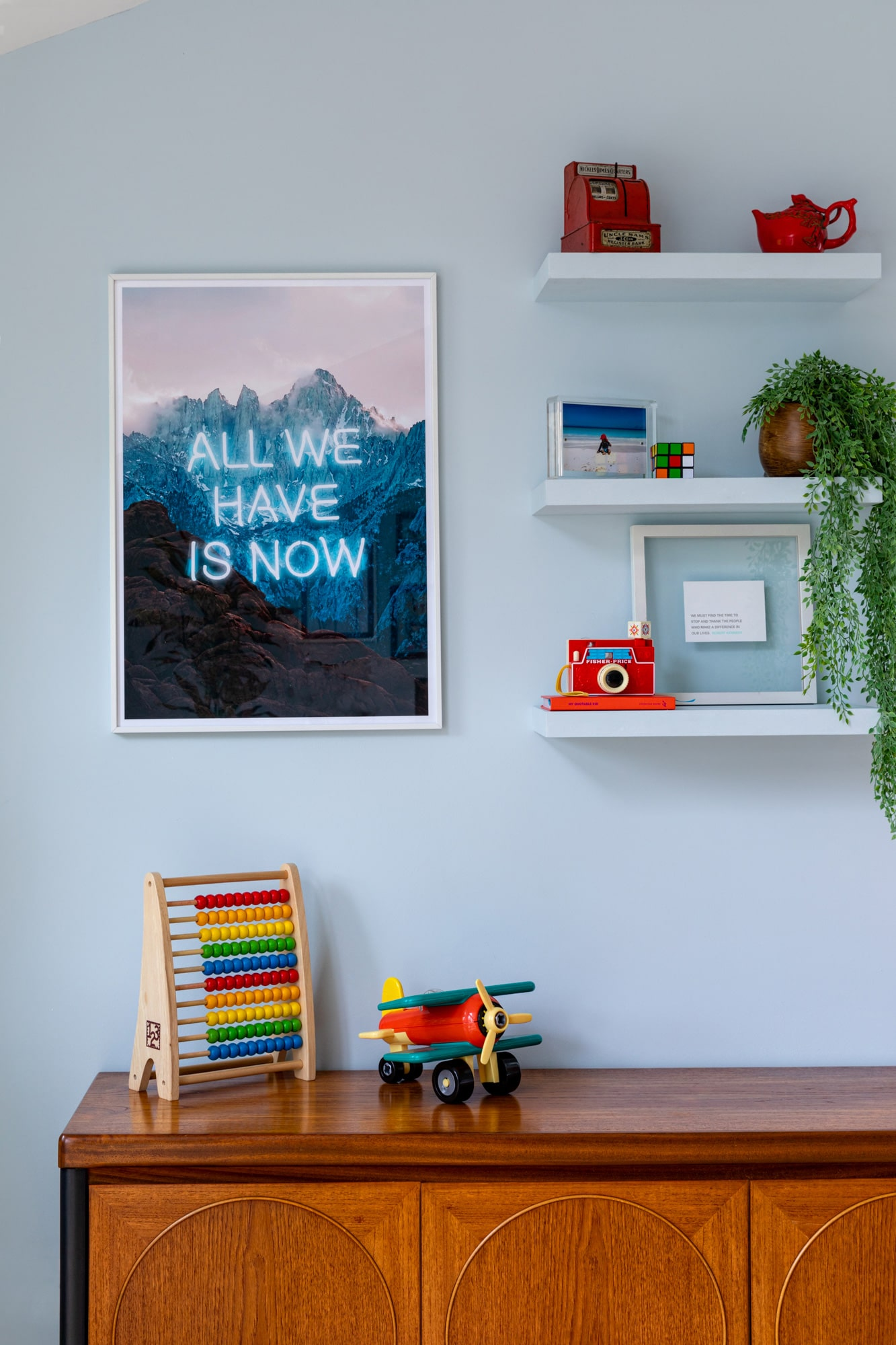 Interior detail photo of a child's play area: wooden cabinet with toys on top; shelves with toys and plant; poster on the wall