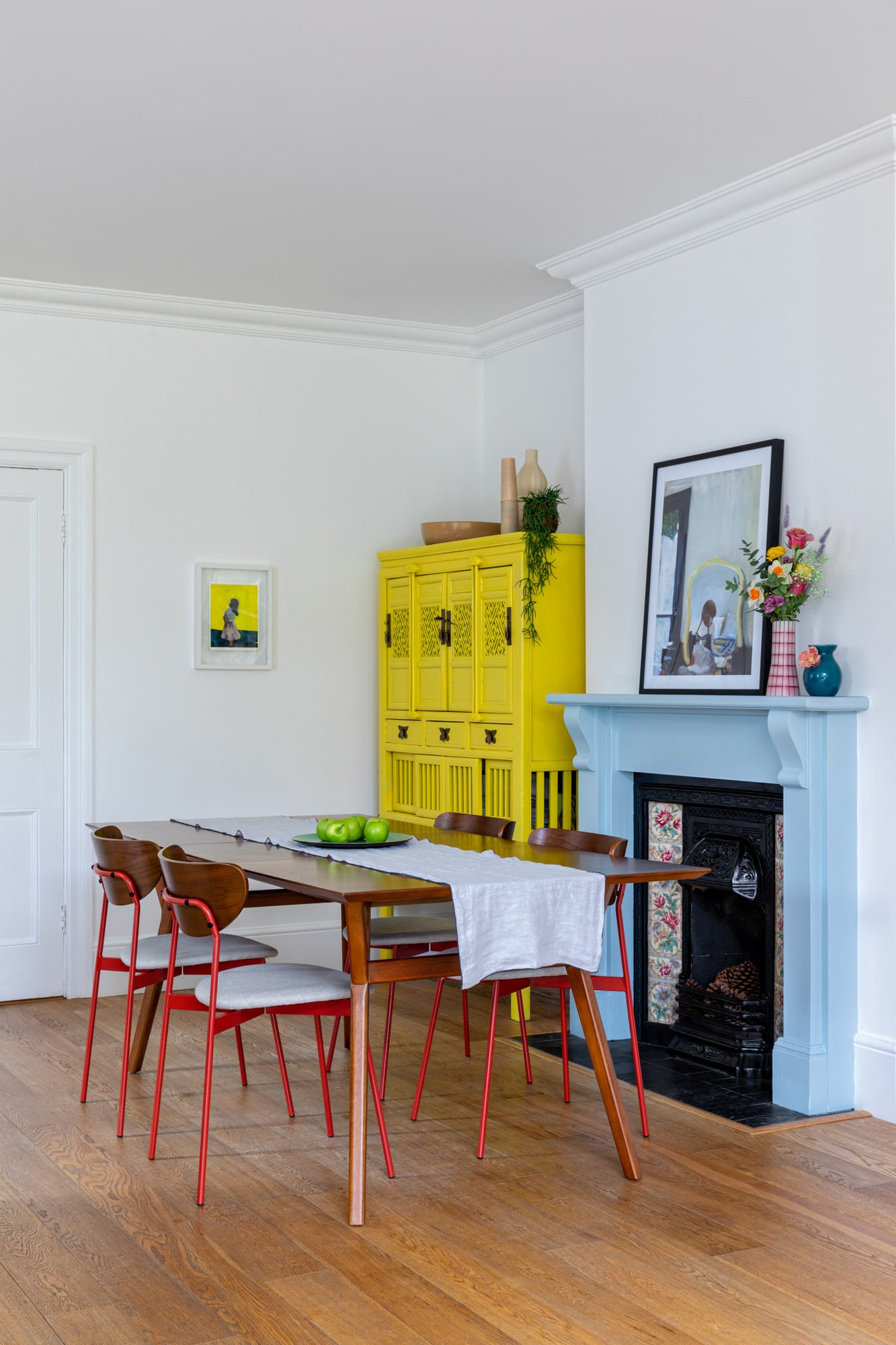 Interior photo of a dining area: blue fireplacewith art and vases on top; yellow cabinet; wooden table and chairs